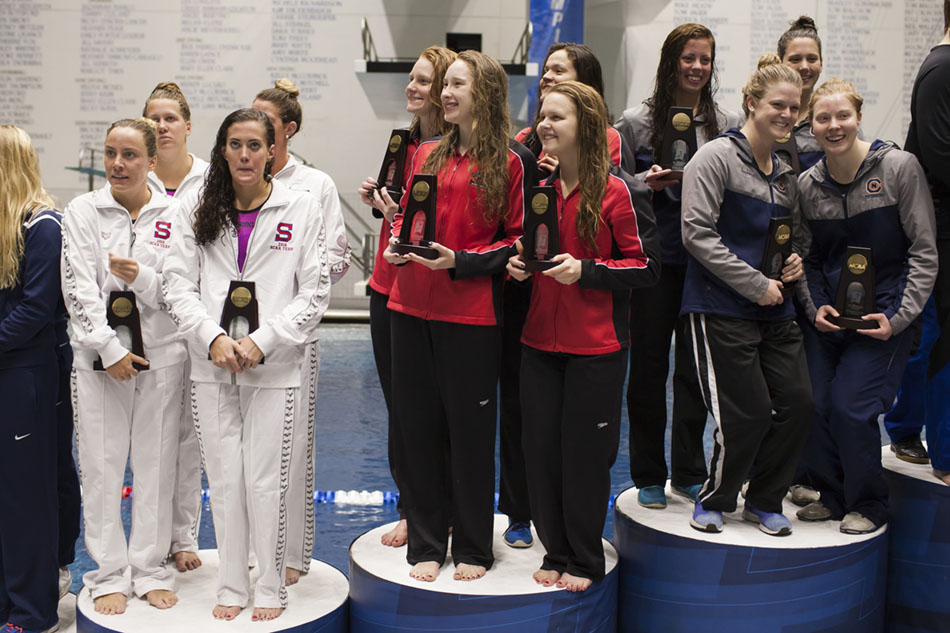 Drury's women's 800-yard freestyle relay team including Sarah Pullen, left, Megan Ouhl, Valentina Carvajal and Laura Brasier hold their trophies on the podium after finishing sixth at the NCAA Division II Swimming and Diving Championships on Friday, March 11, 2016, at the IU Natatorium in Indianapolis. (Photo by James Brosher)