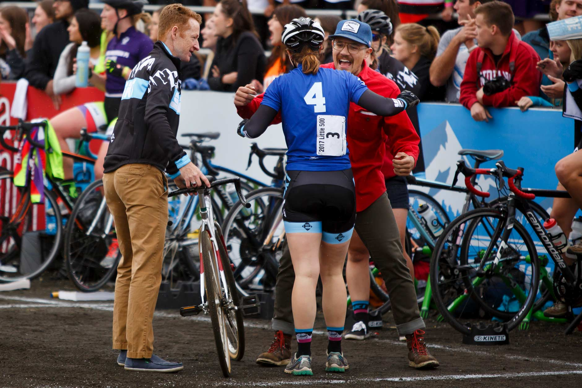 SKI mechanic Sam Harbison, right, hugs rider Ivy Moore (4) as coach Jim Kirkham watches during the Women's Little 500 at Bill Armstrong Stadium on Friday, April 21, 2017. (James Brosher/IU Communications)