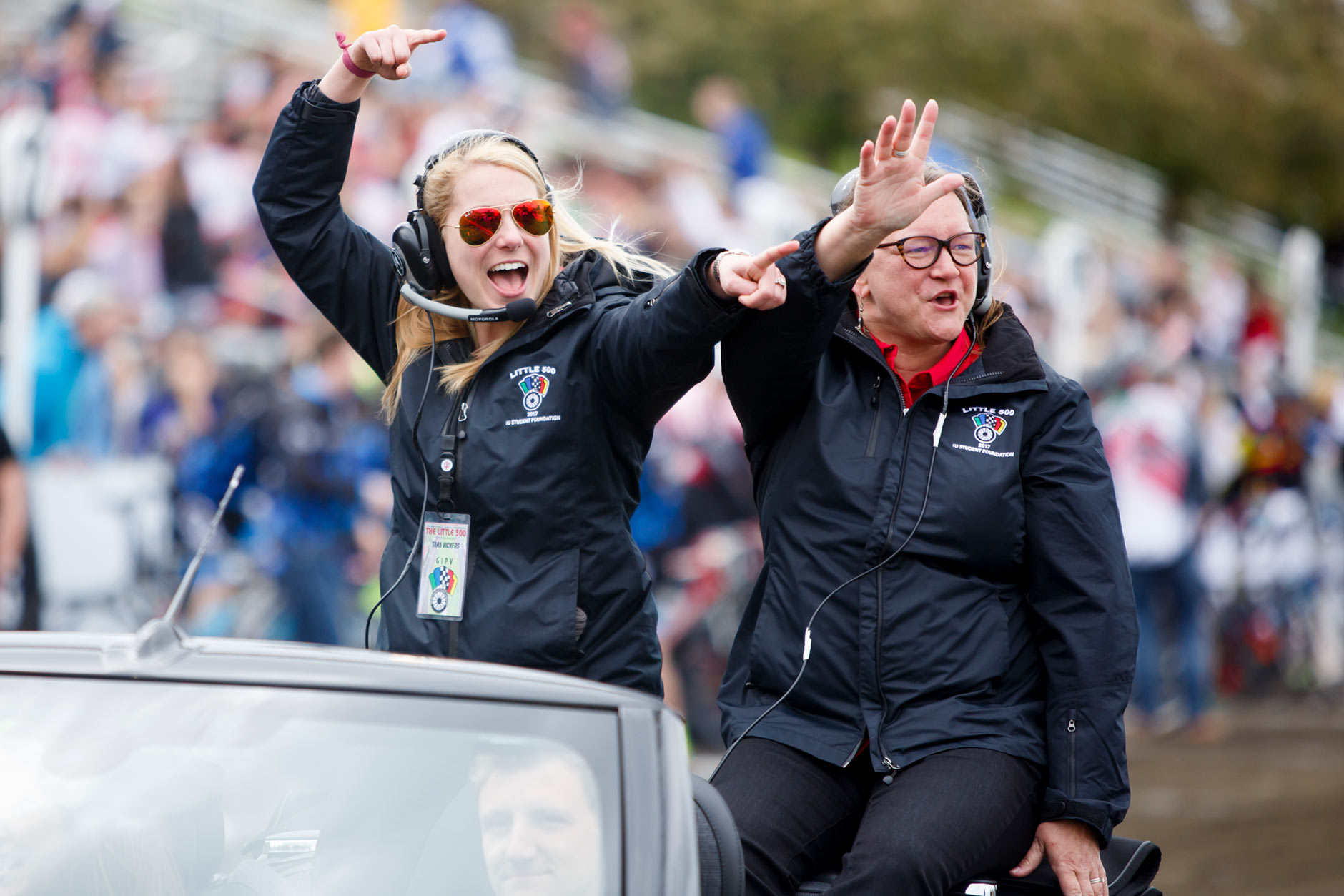 Indiana University Student Foundation Director Tara Vickers, left, and Assistant Director for Operations Bethany Miller wave during the parade lap around the track before the Men's Little 500 at Bill Armstrong Stadium on Saturday, April 22, 2017. (James Brosher/IU Communications)