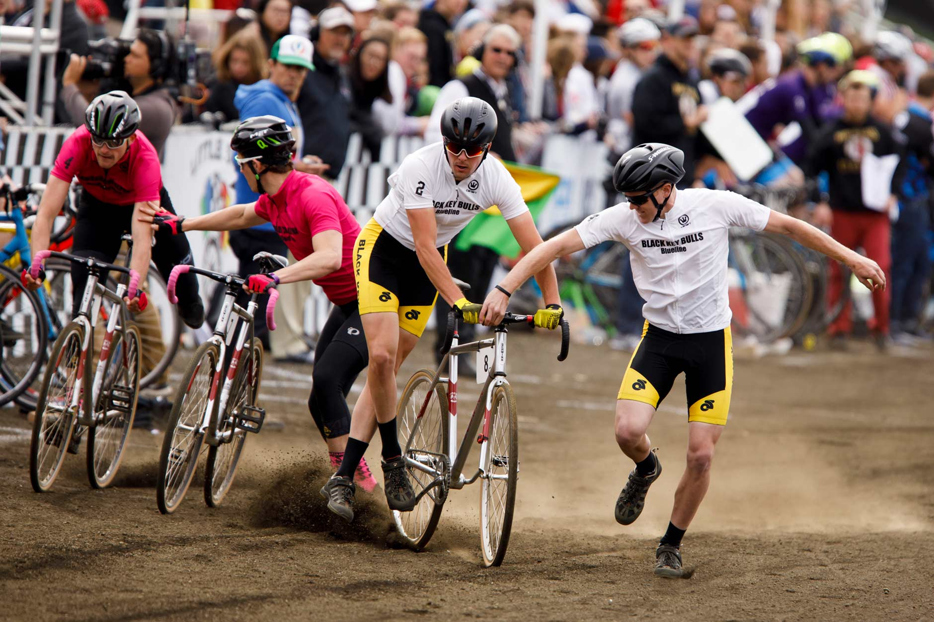 Black Key Bulls rider Charlie Hammon, center, hands off to teammate Kevin Mangel during an exchange late in the Men's Little 500 at Bill Armstrong Stadium on Saturday, April 22, 2017. (James Brosher/IU Communications)