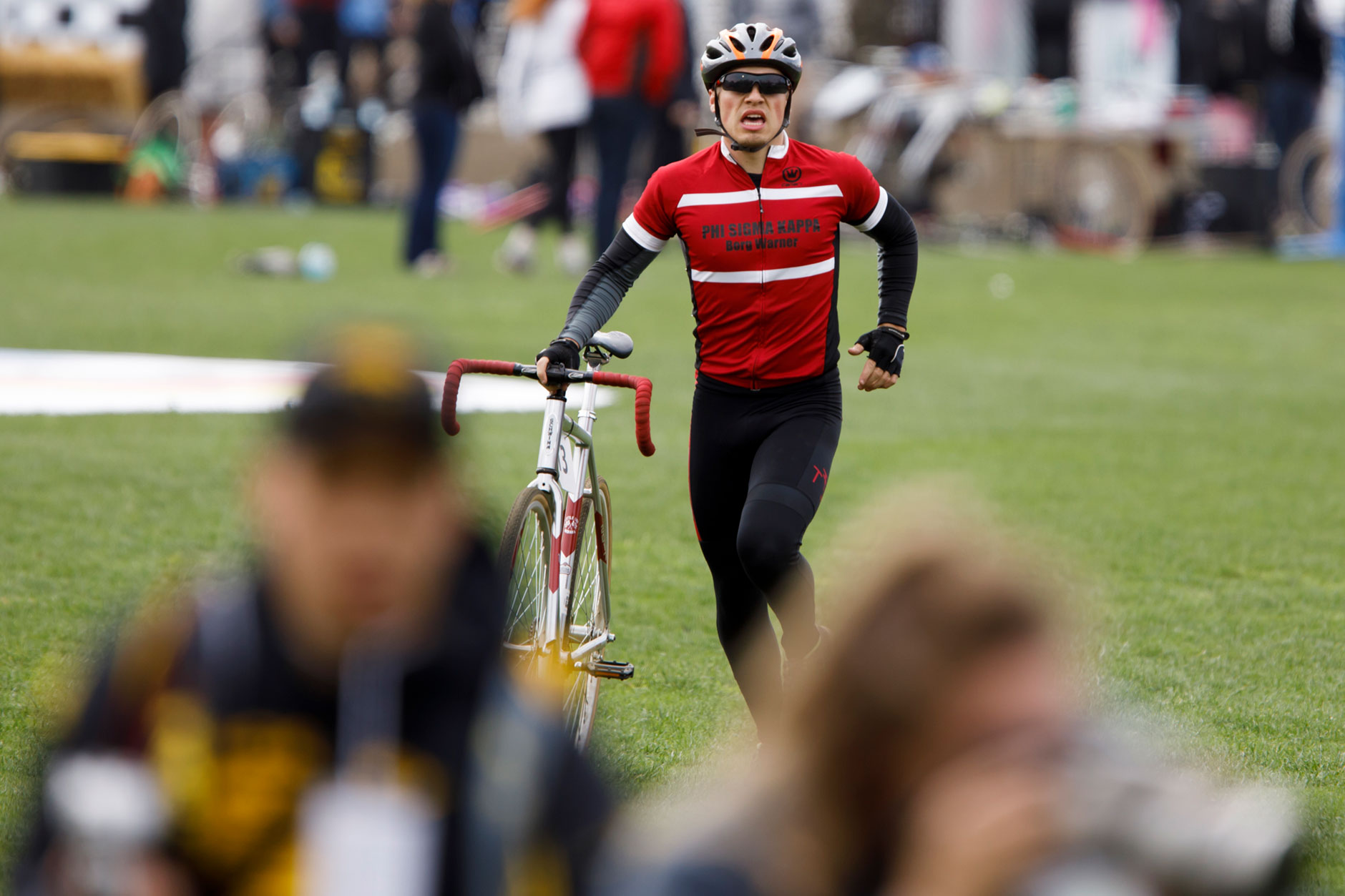 A Phi Sigma Kappa rider races across the infield with a bicycle after a teammate was involved in a crash during the Men's Little 500 at Bill Armstrong Stadium on Saturday, April 22, 2017. (James Brosher/IU Communications)