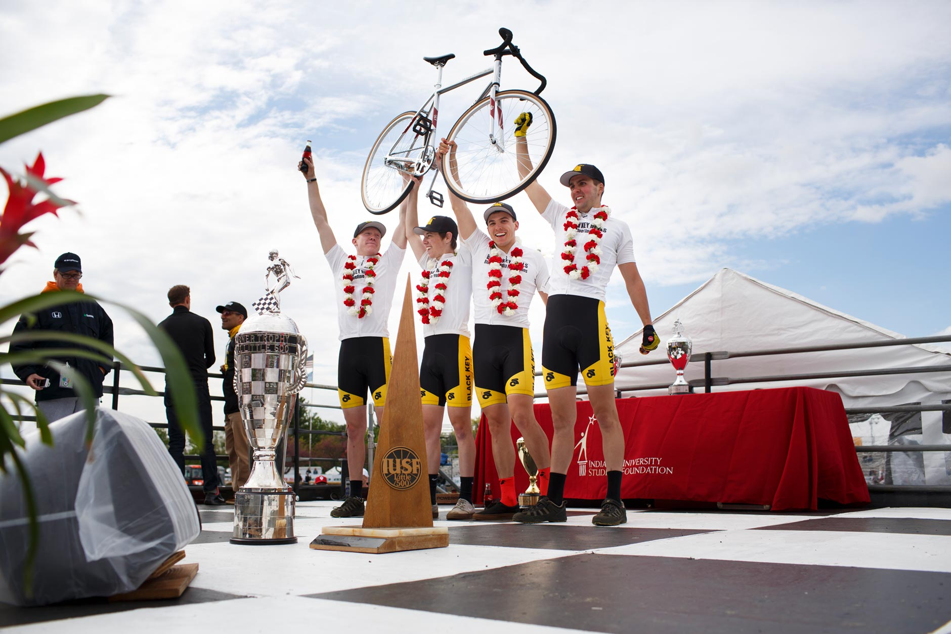 Black Key Bulls riders Kevin Mangel, left, Noah Voyles, Xavier Martinez and Charlie Hammon hoist a Schwinn bicycle above their heads in celebration after winning the Men's Little 500 at Bill Armstrong Stadium on Saturday, April 22, 2017. (James Brosher/IU Communications)