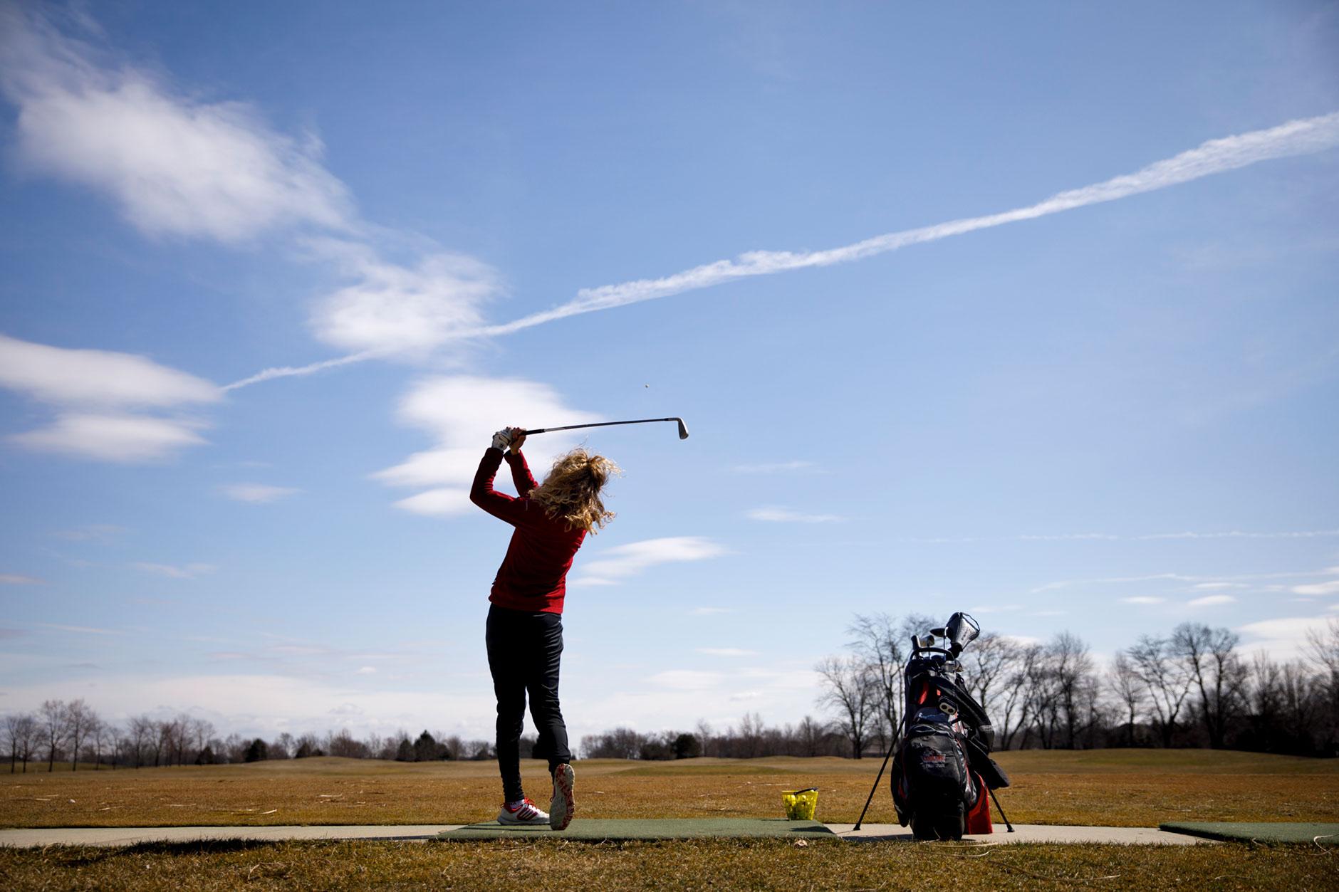 Bailey Troutman, a graduating senior at IU Kokomo, hits a golf ball on the range at Wildcat Creek Golf Course in Kokomo on Wednesday, March 21, 2018. (James Brosher/IU Communications)