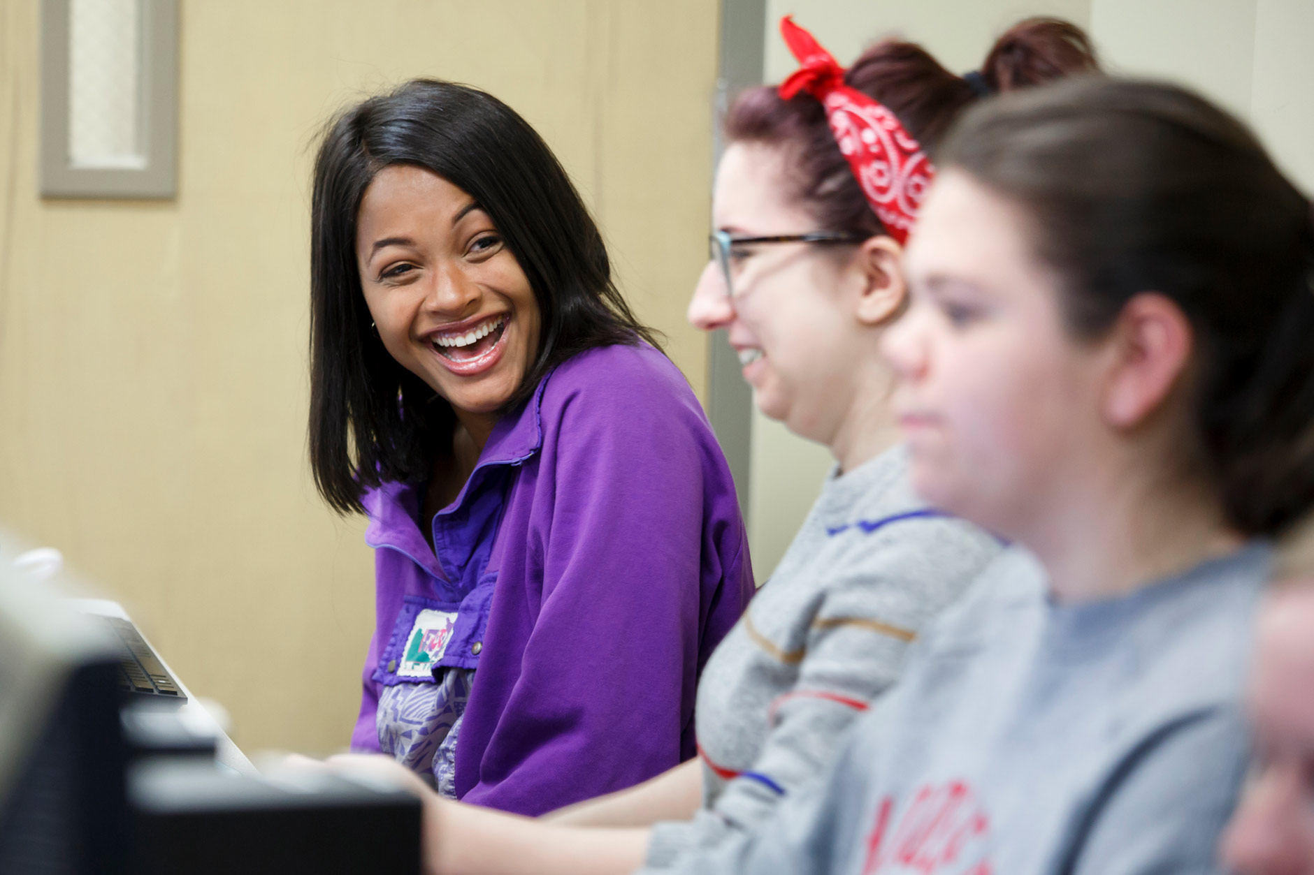 Mica Caine, a graduating senior at IU Bloomington, laughs with friends before a class in Hodge Hall at the Kelley School of Business in Bloomington on Wednesday, April 4, 2018. (James Brosher/IU Communications)