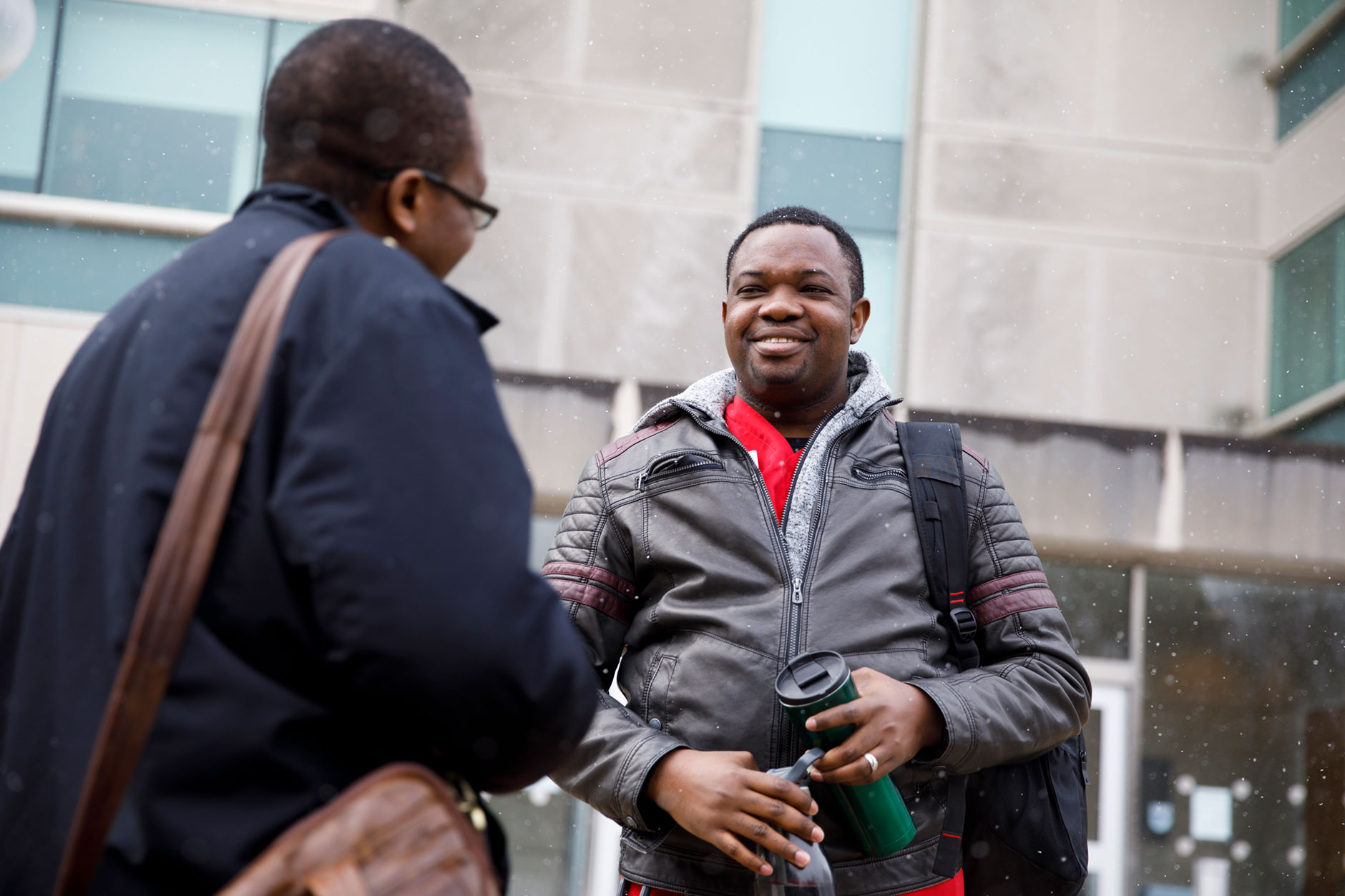 Desmond Atem, a graduating senior at IU South Bend, speaks with a colleague outside of Schurz Library on Monday, April 9, 2018. (James Brosher/IU Communications)