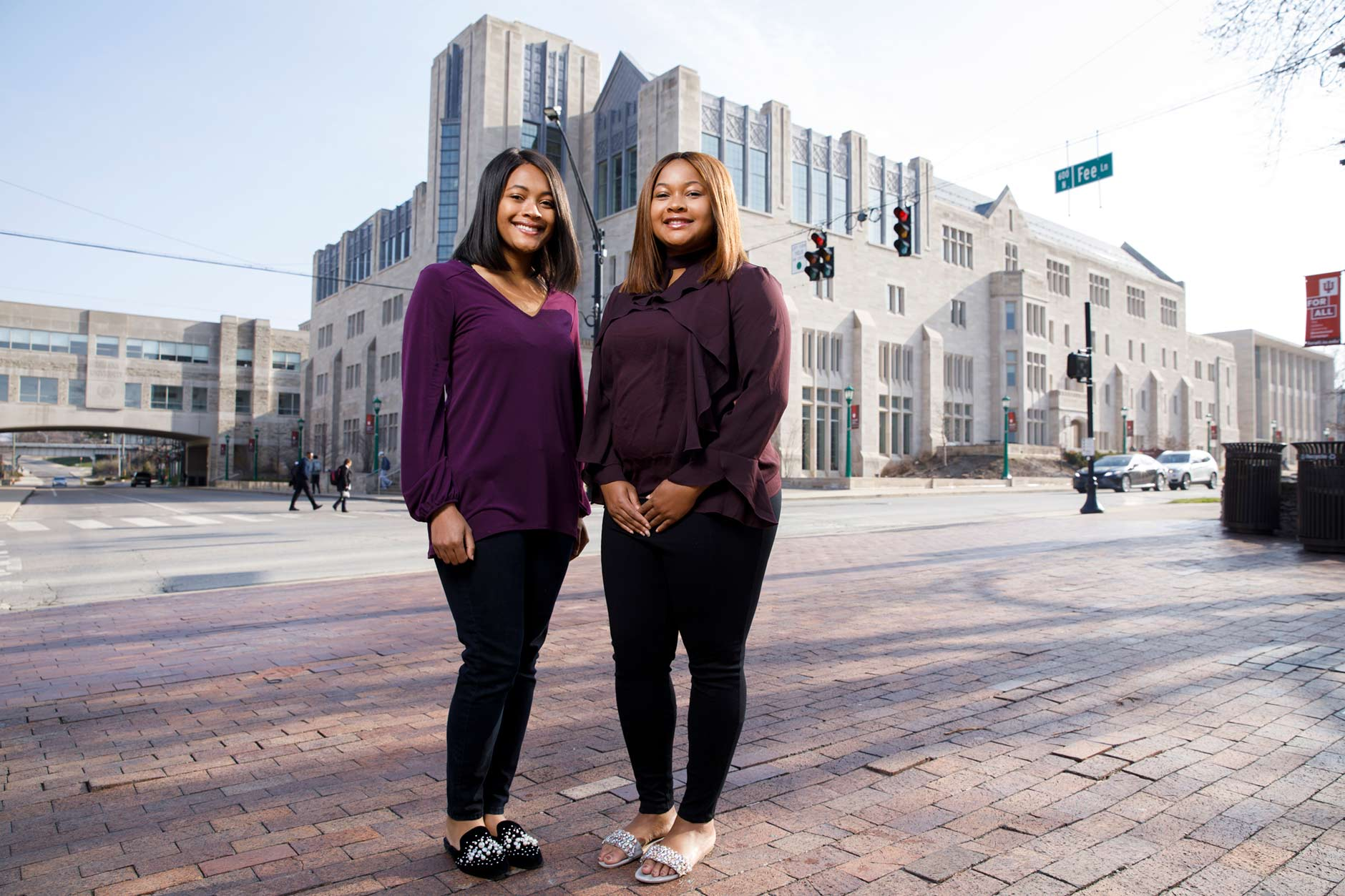 Sisters Mica, left, and Maya Caine, graduating seniors at IU Bloomington, pose for a portrait outside of Hodge Hall at the Kelley School of Business in Bloomington on Tuesday, April 10, 2018. (James Brosher/IU Communications)