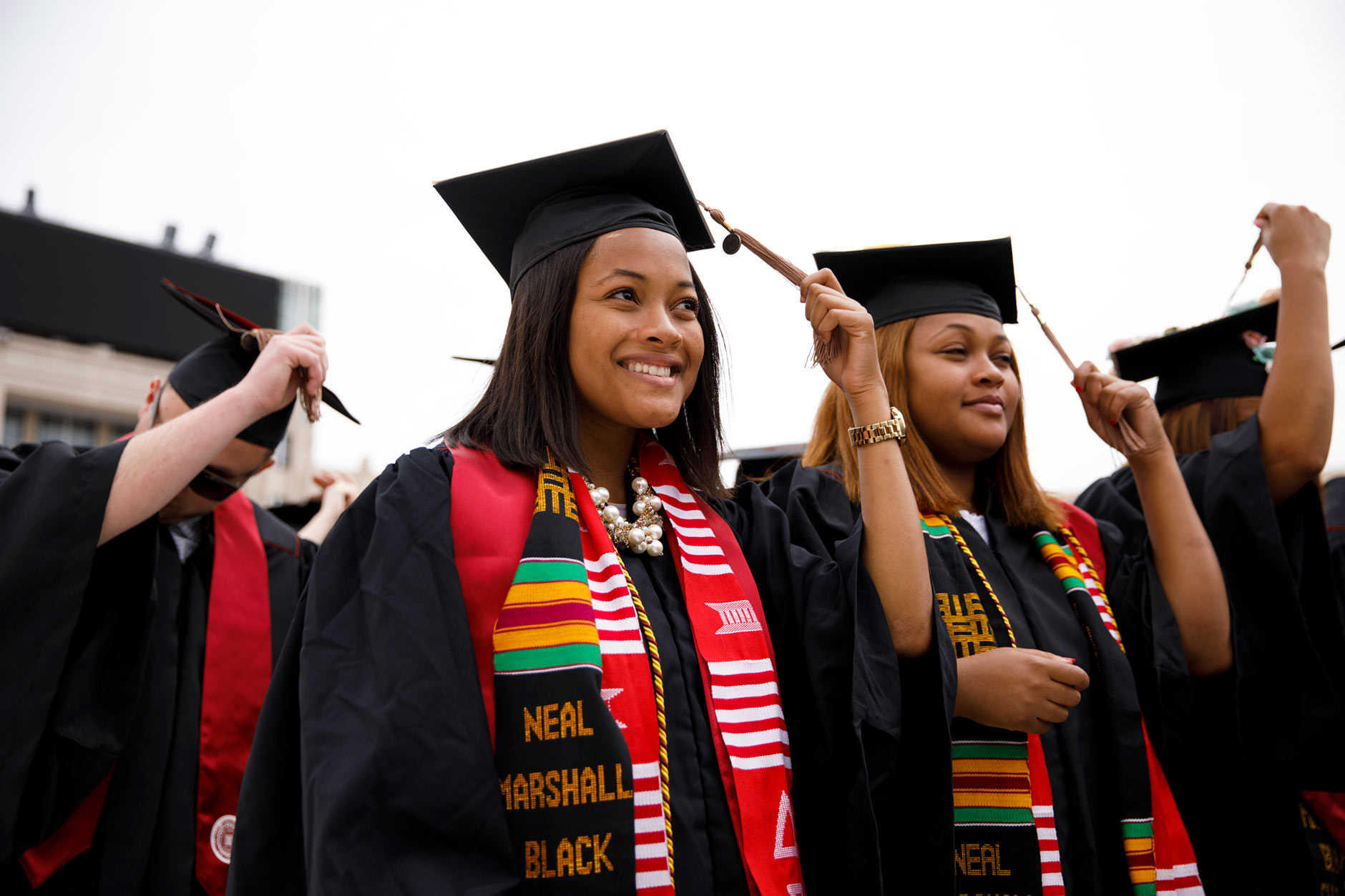 Graduating sisters Mica, left, and Maya Caine move their tassels to the left to mark their graduation from the Indiana University Kelley School of Business during the IU Bloomington Undergraduate Commencement in Memorial Stadium on Saturday, May 5, 2018. (James Brosher/IU Communications)