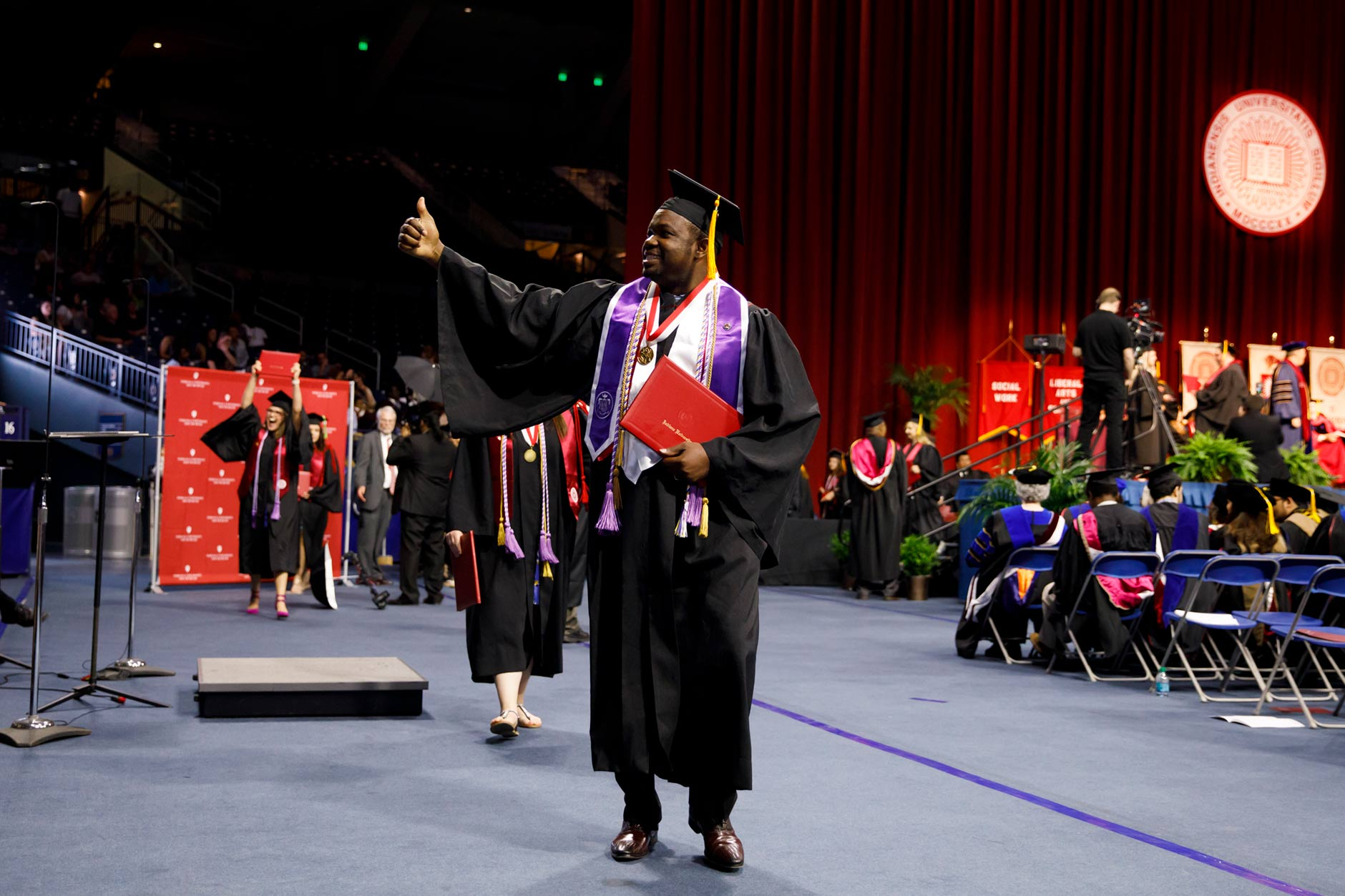 Graduate Desmond Atem reacts to family in the audience after receiving his diploma during the Indiana University South Bend Commencement at the University of Notre Dame on Tuesday, May 8, 2018. (James Brosher/IU Communications)