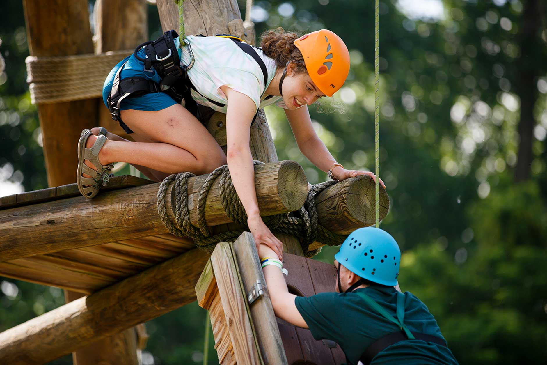 Indiana University student Maria Erlandson, a junior studying recreational therapy, encourages a camper on a challenge course at Bradford Woods on Thursday, May 31, 2018. (James Brosher/IU Communications)