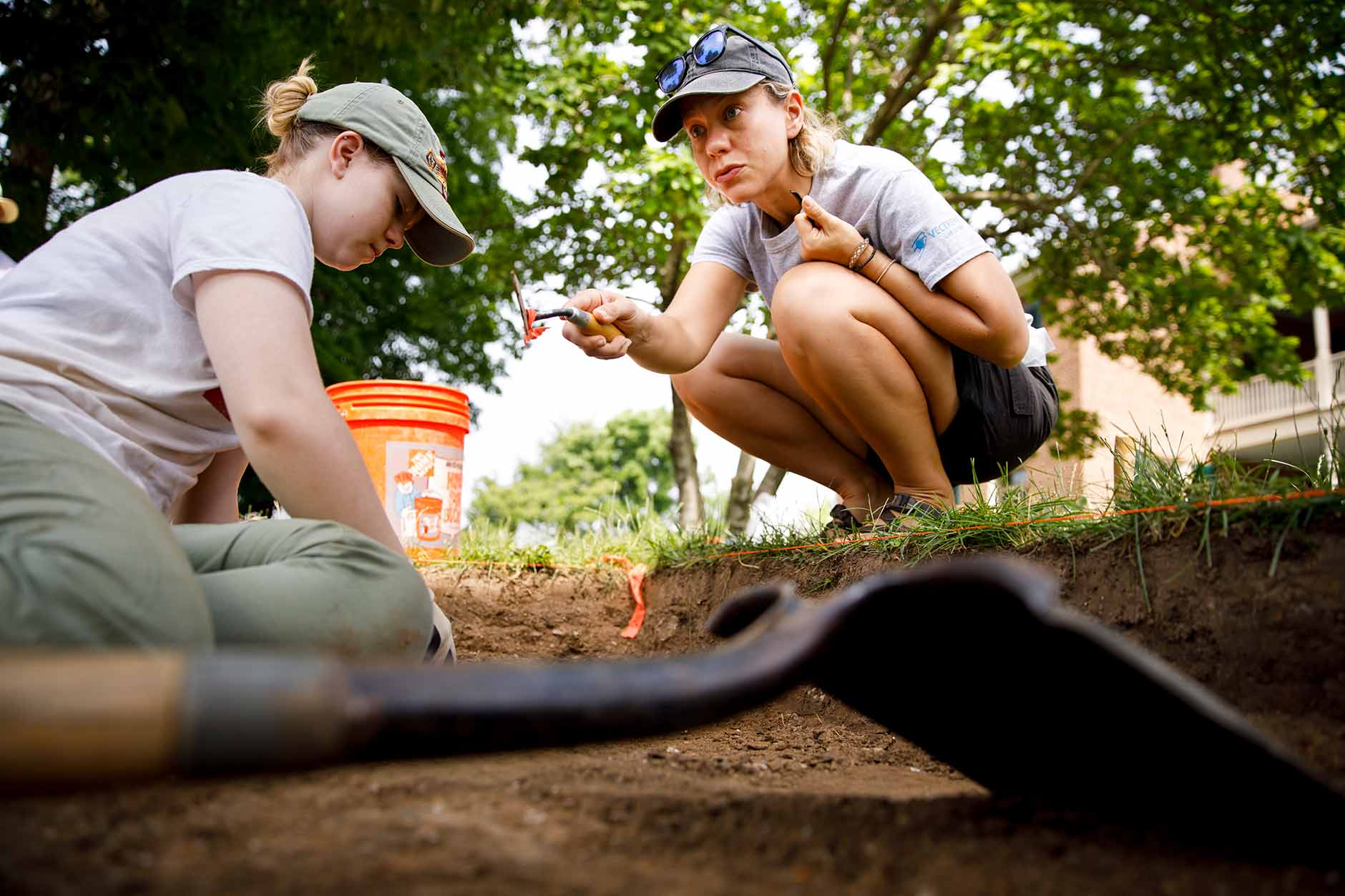 Elizabeth Watts Malouchos, right, a research scientist at the Indiana University Glenn A. Black Laboratory of Archaeology, works with IU sophomore Lauren Schumacher during an archaeological project at Wylie House in Bloomington on Thursday, June 7, 2018. During the four week field school, students will learn archaeological field methods from Glenn A. Black Laboratory of Archaeology researchers while searching for two buried garden facilities dating to 1859. (James Brosher/IU Communications)