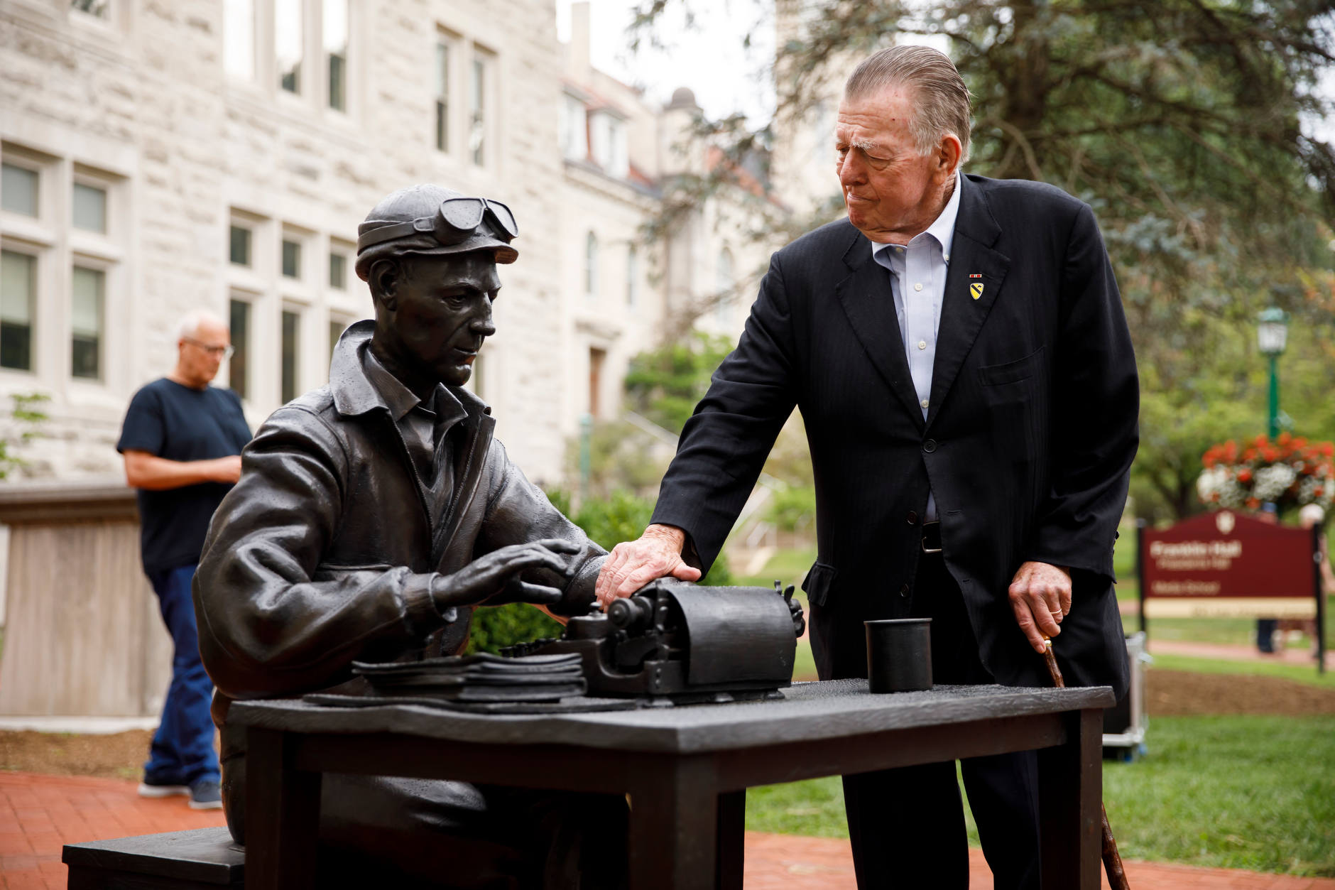 War correspondent Joseph Galloway, right, inspects the sculpture of Ernie Pyle outside of Franklin Hall during an event celebrating National Ernie Pyle Day at The Media School at Indiana University on Friday, Aug. 3, 2018. (James Brosher/IU Communications)