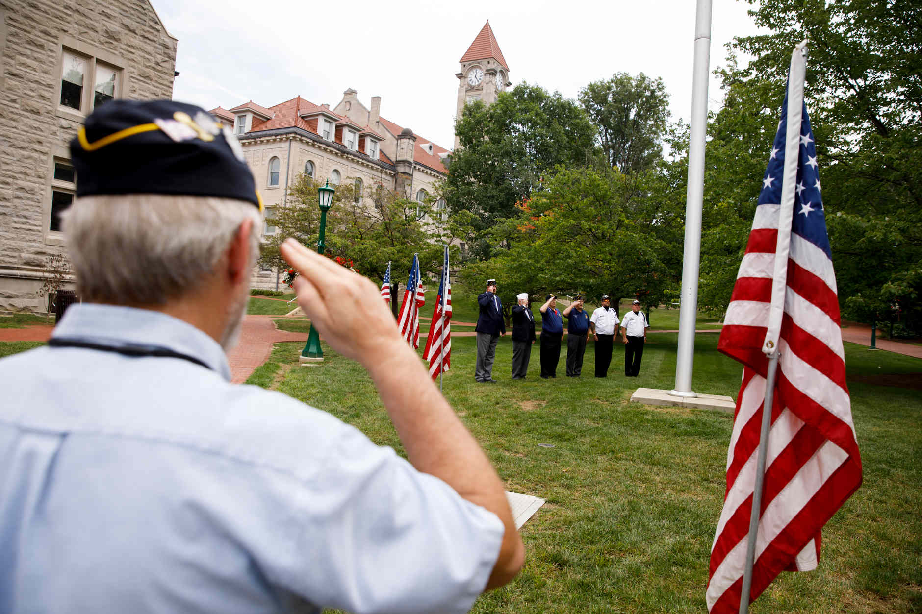 A veteran salutes as an honor guard raises a flag outside of Franklin Hall during an event celebrating National Ernie Pyle Day at The Media School at Indiana University on Friday, Aug. 3, 2018. (James Brosher/IU Communications)