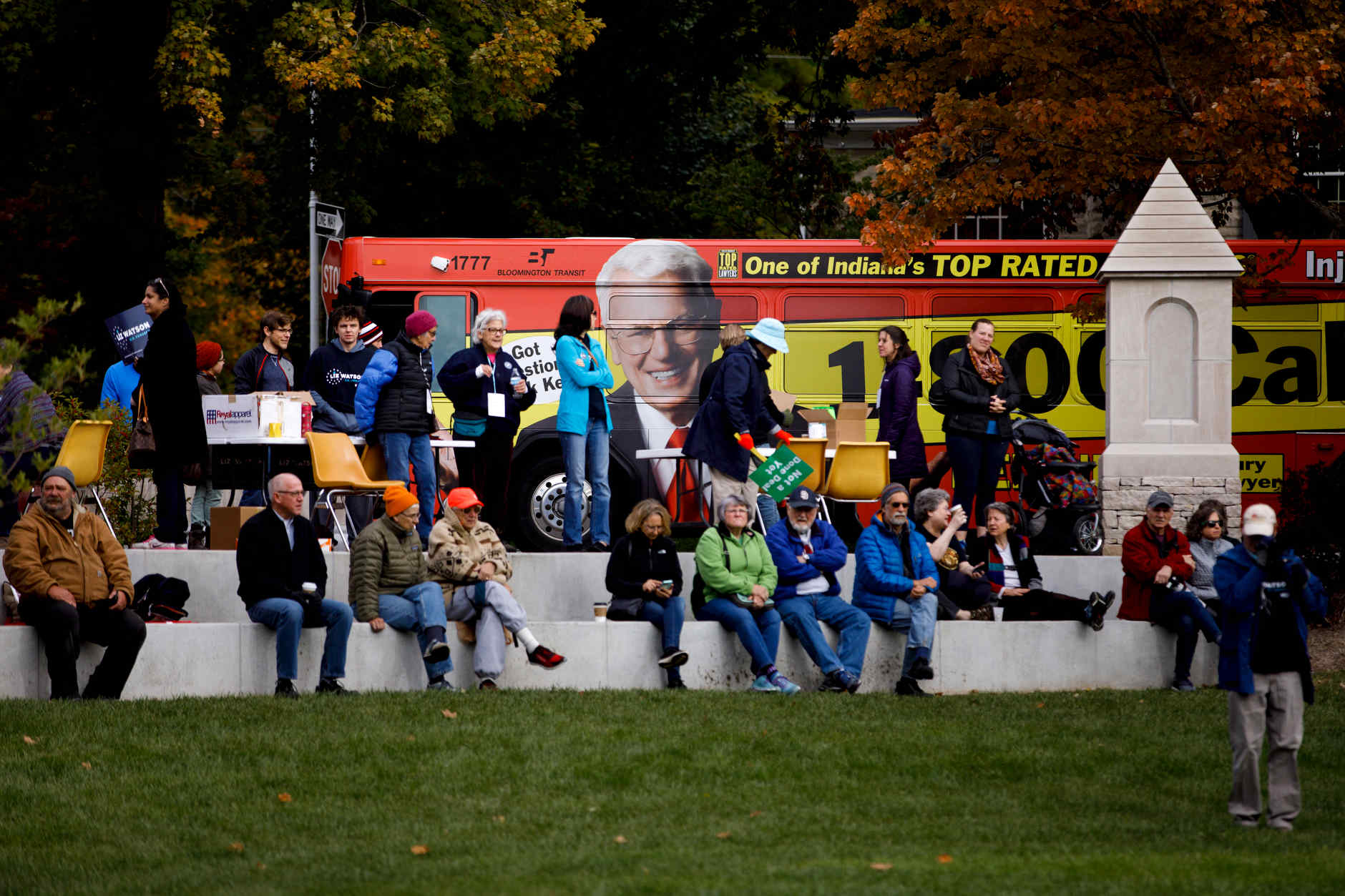 A bus featuring the image of Ken Nunn, a local personal injury lawyer, passes as supporters await the arrival of U.S. Sen. Bernie Sanders, I-VT, at a rally for Liz Watson, the Democratic nominee for Indiana's 9th congressional district, in Dunn Meadow at Indiana University Bloomington on Friday, Oct. 19, 2018. (James Brosher/IU Communications)