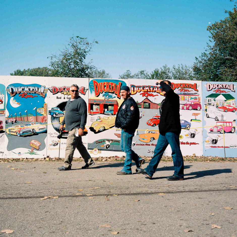 Men walk past boards showing past logos for the Ducktail Run Rod and Custom Show in Gas City, Indiana on Saturday, Sept. 29, 2018. (Photo by James Brosher)