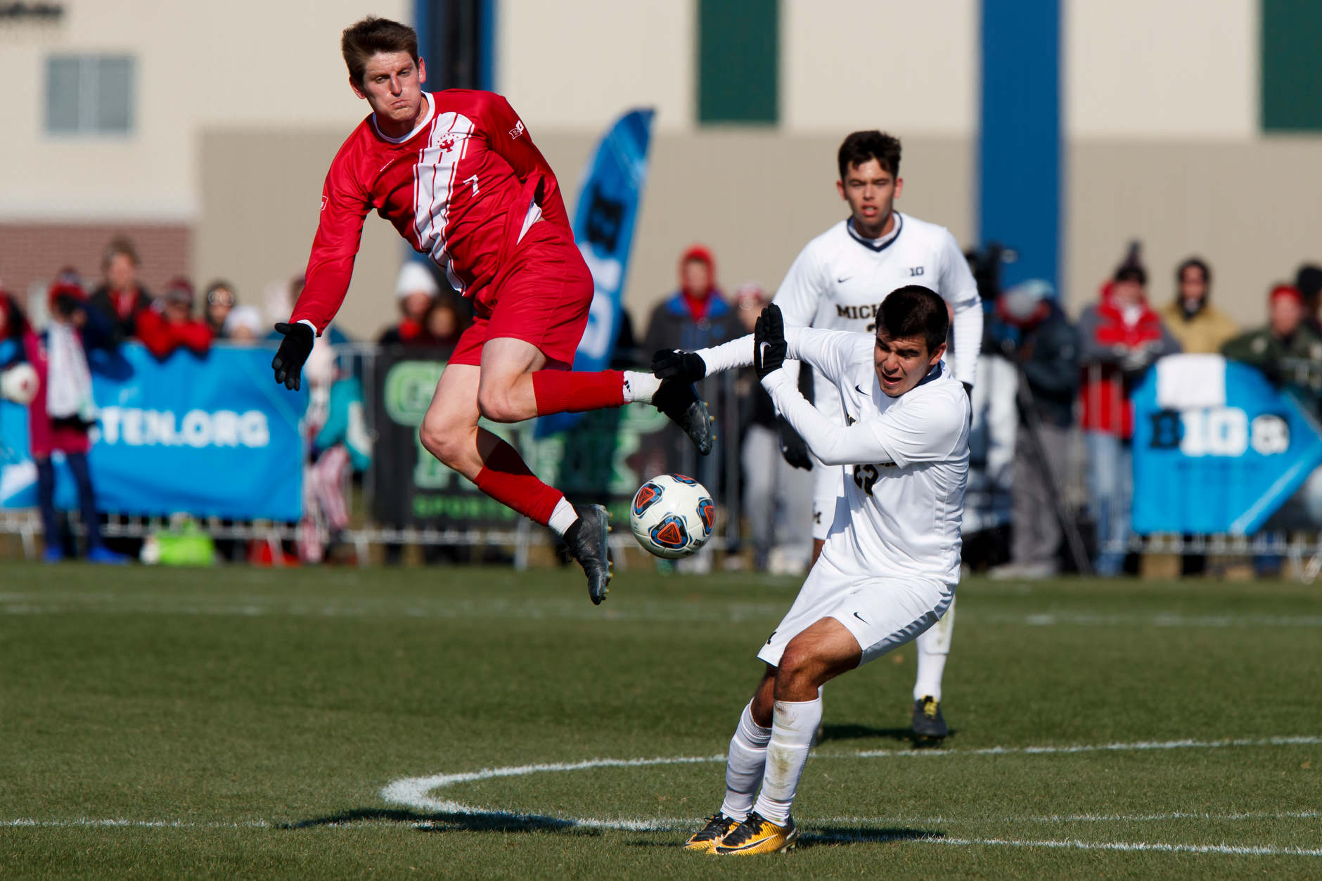 Michigan's Marc Ybarra (23) tries to avoid contact from Indiana's Trevor Swartz (7) during the Big Ten Men's Soccer Tournament championship game at Grand Park in Westfield, Indiana on Sunday, Nov. 11, 2018. (Photo by James Brosher)