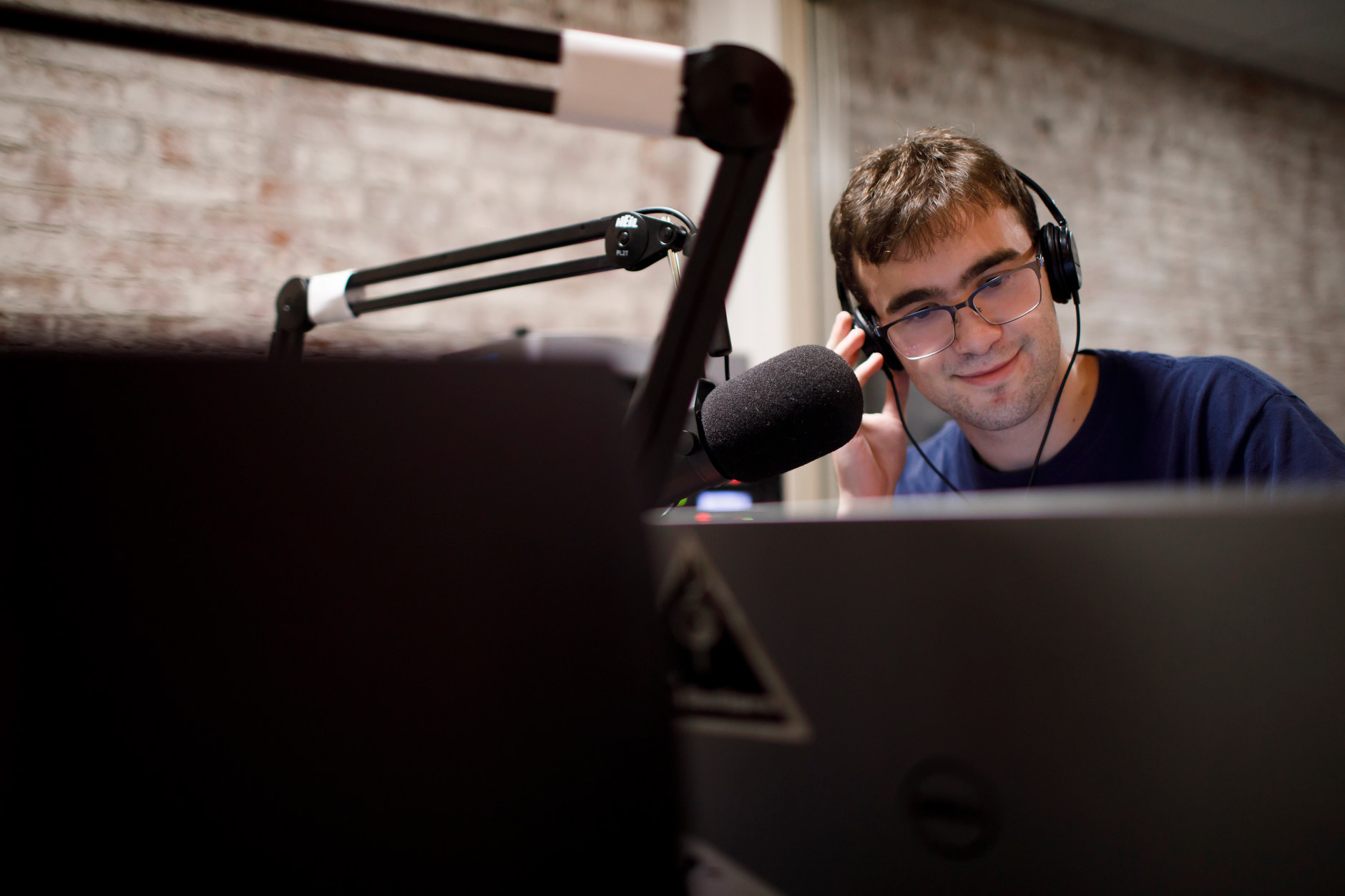 Patrick Spanier interviews a musician on the phone during a live broadcast in the WIUX studios in Franklin Hall on Tuesday, Sept. 25, 2018.