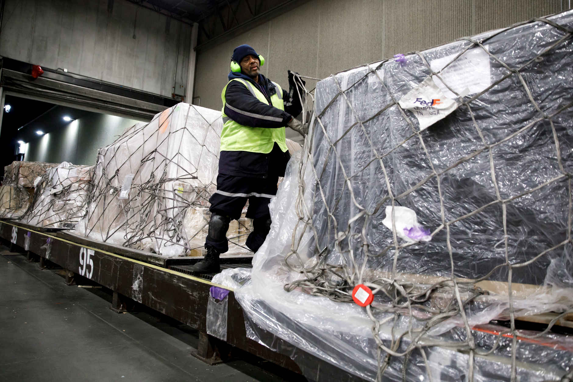 James Wilson, a FedEx material handler, secures cargo netting over a stack of packages at the FedEx Express Hub in Indianapolis in the early morning hours of Wednesday, Feb. 27, 2019. (James Brosher for The Wall Street Journal)