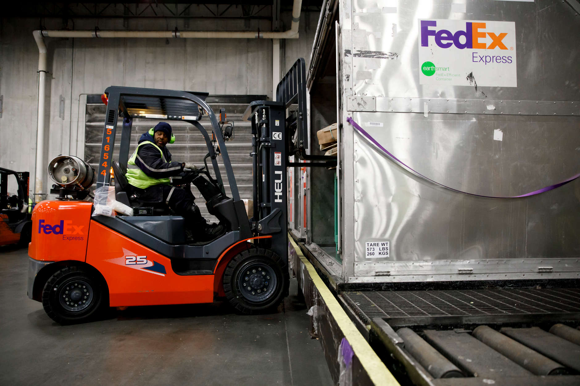 James Wilson, a FedEx material handler, carefully maneuvers a pallet of packages into a unit load device (ULD) using a forklift at the FedEx Express Hub in Indianapolis in the early morning hours of Wednesday, Feb. 27, 2019. (James Brosher for The Wall Street Journal)