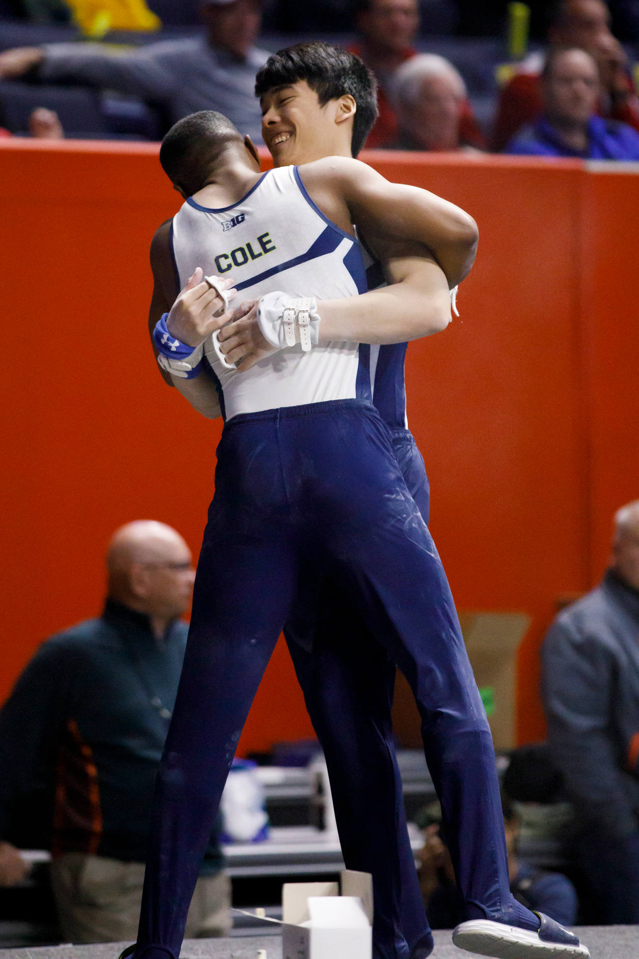 Michigan's Emyre Cole, left, hugs teammate Johnathan Liu after Liu competed on the high bar at the NCAA Men's Gymnastics Championships on Friday, April 19, 2019, at the State Farm Center in Champaign, Illinois. (Photo by James Brosher)