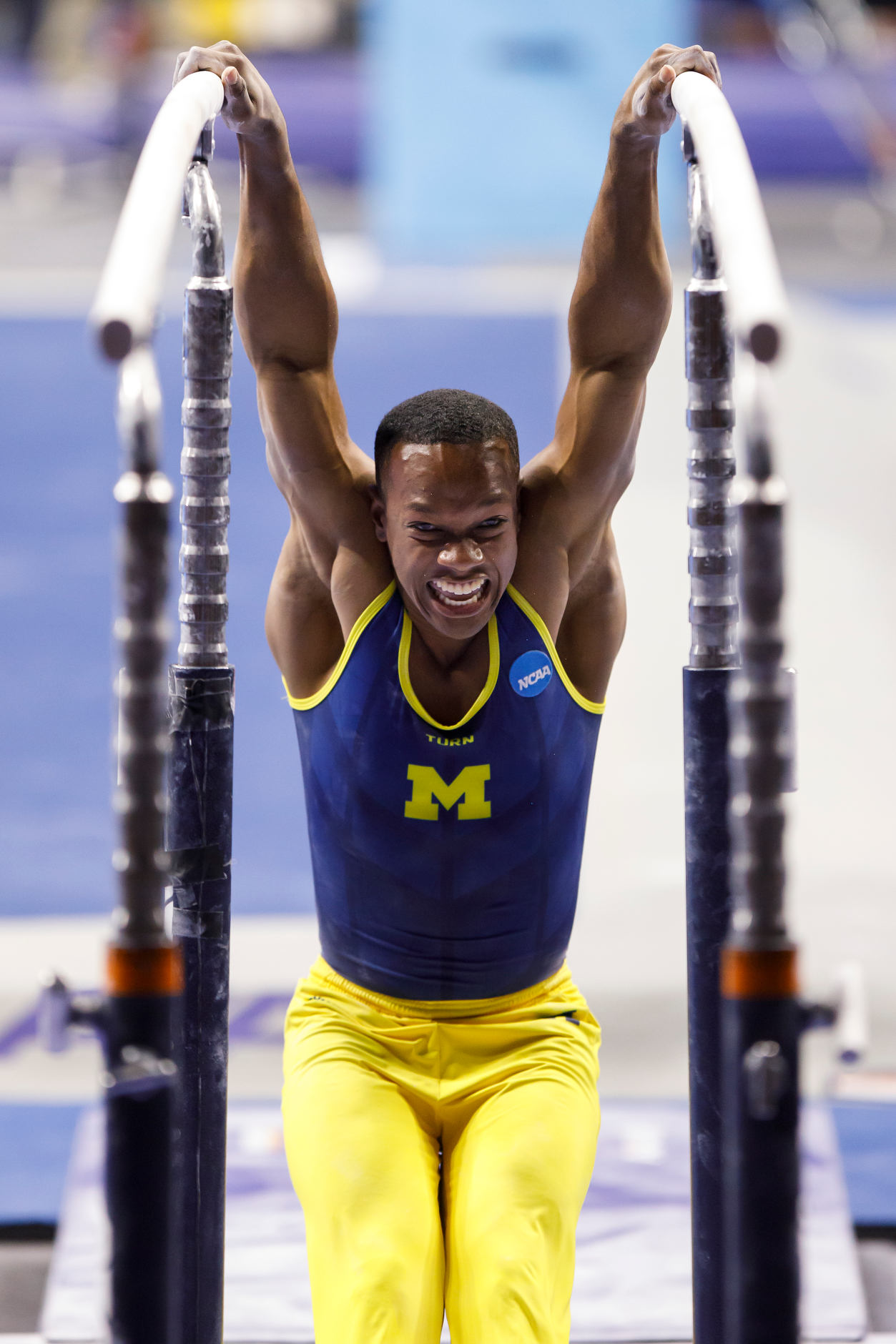Michigan's Emyre Cole competes on the parallel bars at the NCAA Men's Gymnastics Championships on Saturday, April 20, 2019, at the State Farm Center in Champaign, Illinois. (Photo by James Brosher)