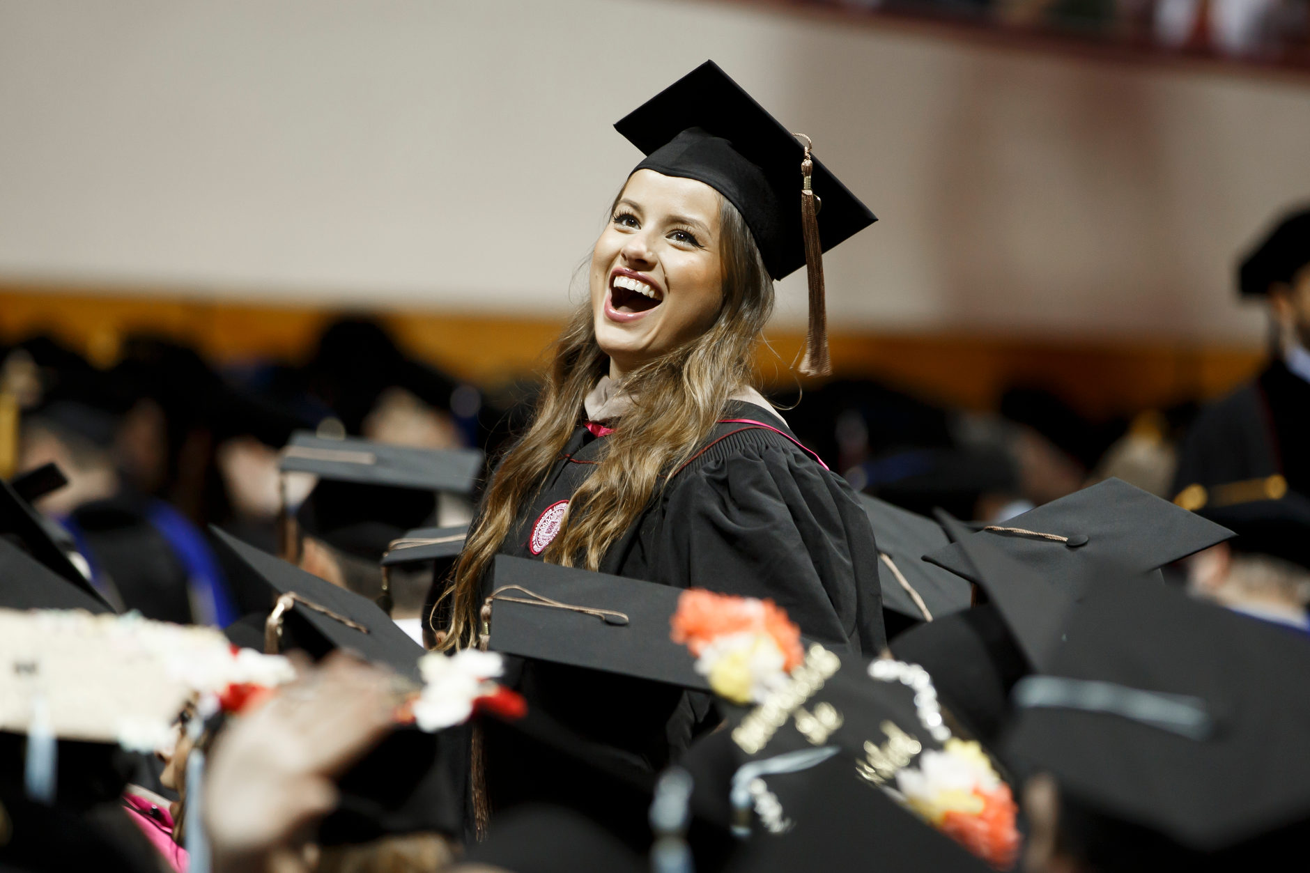 A graduate yells to friends in the audience before the Indiana University Bloomington Graduate Commencement at Assembly Hall on Friday, May 3, 2019. (James Brosher/Indiana University)