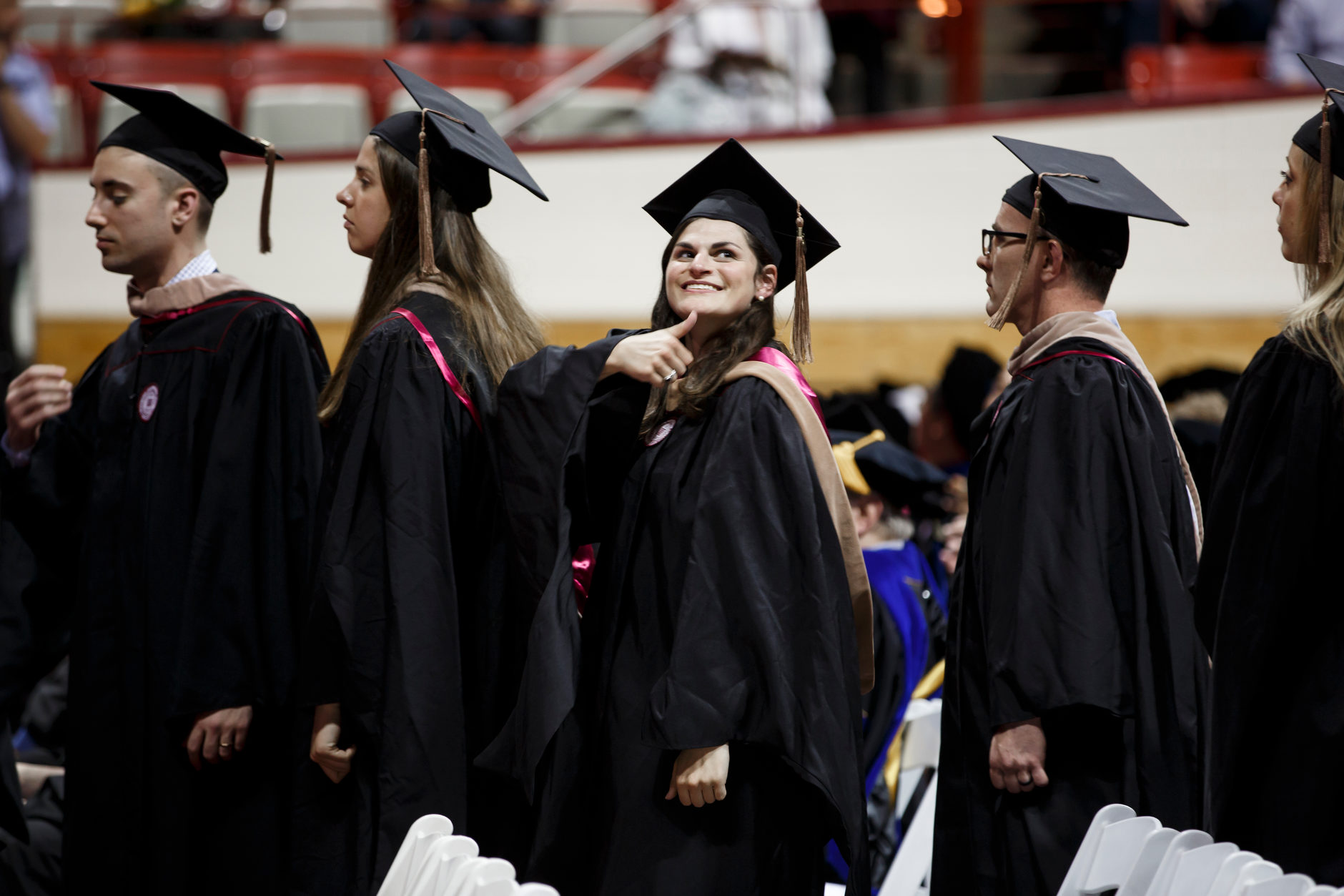 A graduate gives friends in the audience a thumbs up during the Indiana University Bloomington Graduate Commencement at Assembly Hall on Friday, May 3, 2019. (James Brosher/Indiana University)