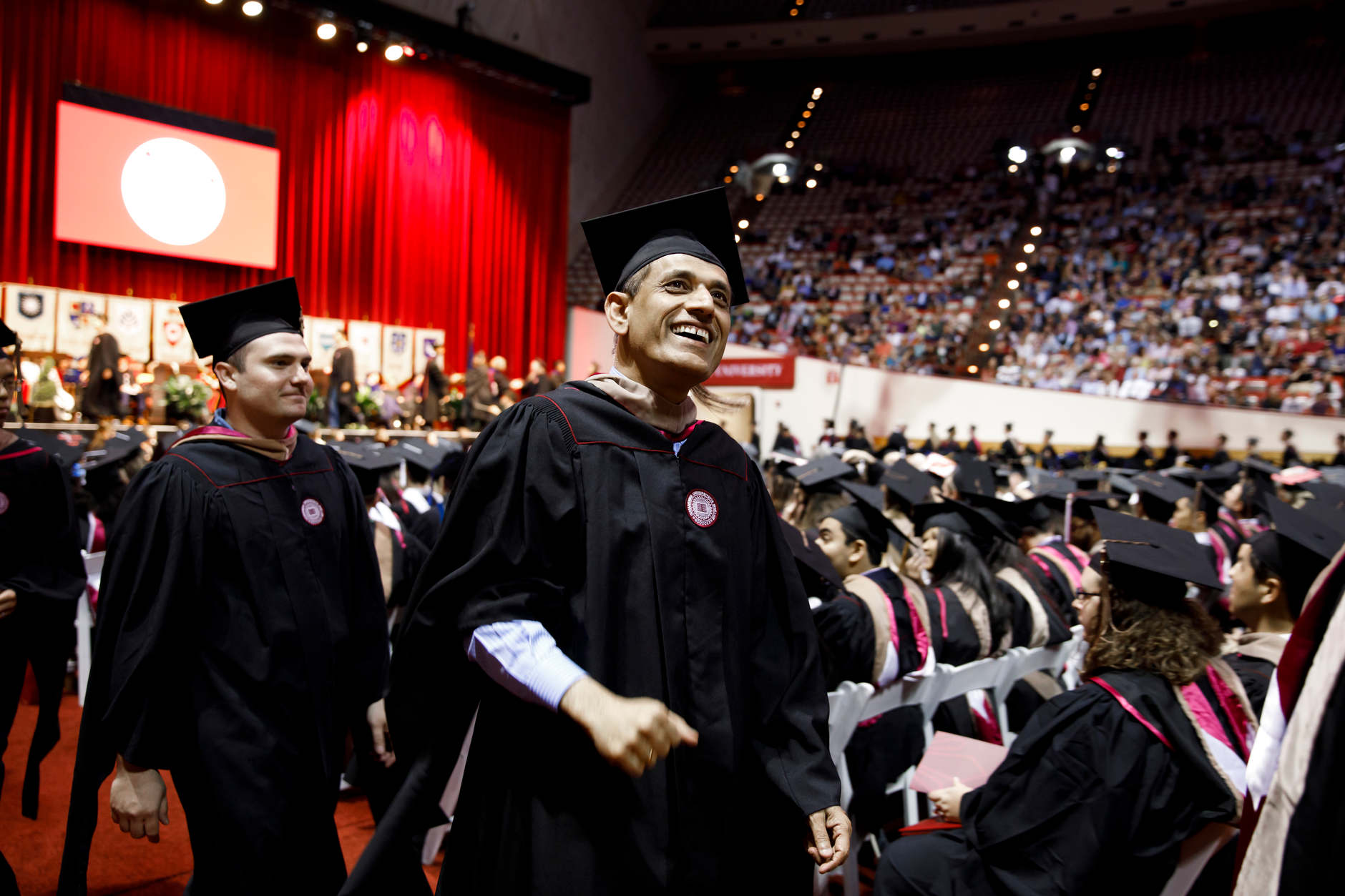 A graduate smiles as he reacts to friends in the audience during the Indiana University Bloomington Graduate Commencement at Assembly Hall on Friday, May 3, 2019. (James Brosher/Indiana University)