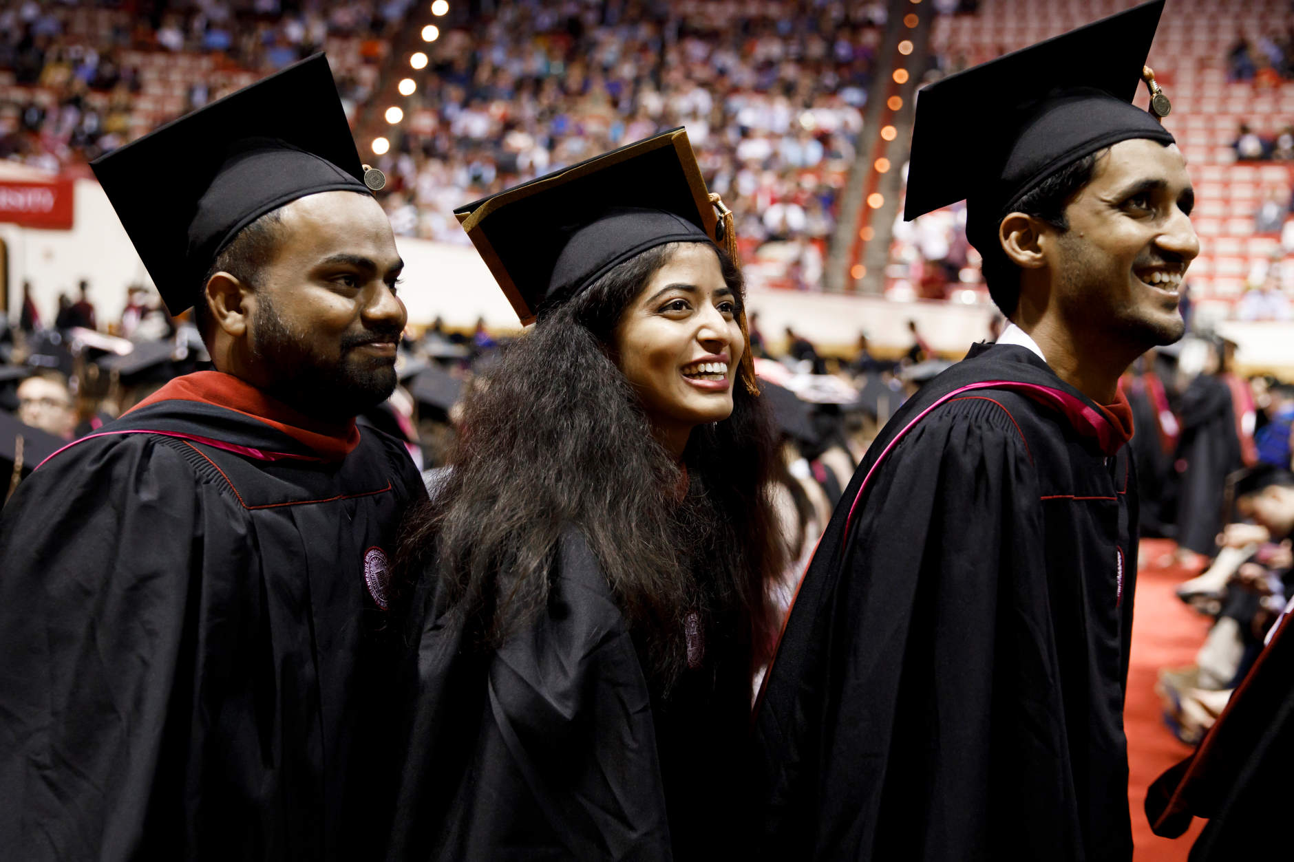 Graduates smile as friends in the audience cheer during the Indiana University Bloomington Graduate Commencement at Assembly Hall on Friday, May 3, 2019. (James Brosher/Indiana University)