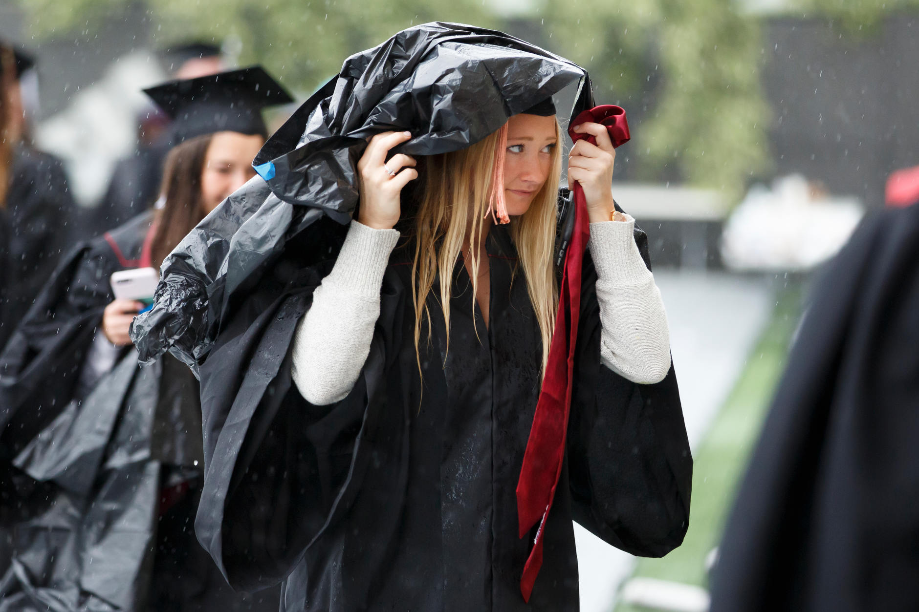 A graduate shields herself from the rain as she files into Mellencamp Pavilion before the Indiana University Bloomington Undergraduate Commencement on Saturday, May 4, 2019. (James Brosher/Indiana University)