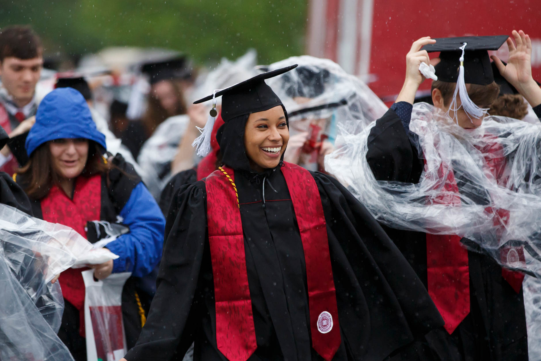 A graduate smiles as she walks through the rain during the processional for the IU Bloomington Undergraduate Commencement from Mellencamp Pavilion to Memorial Stadium on Saturday, May 4, 2019. (James Brosher/Indiana University)