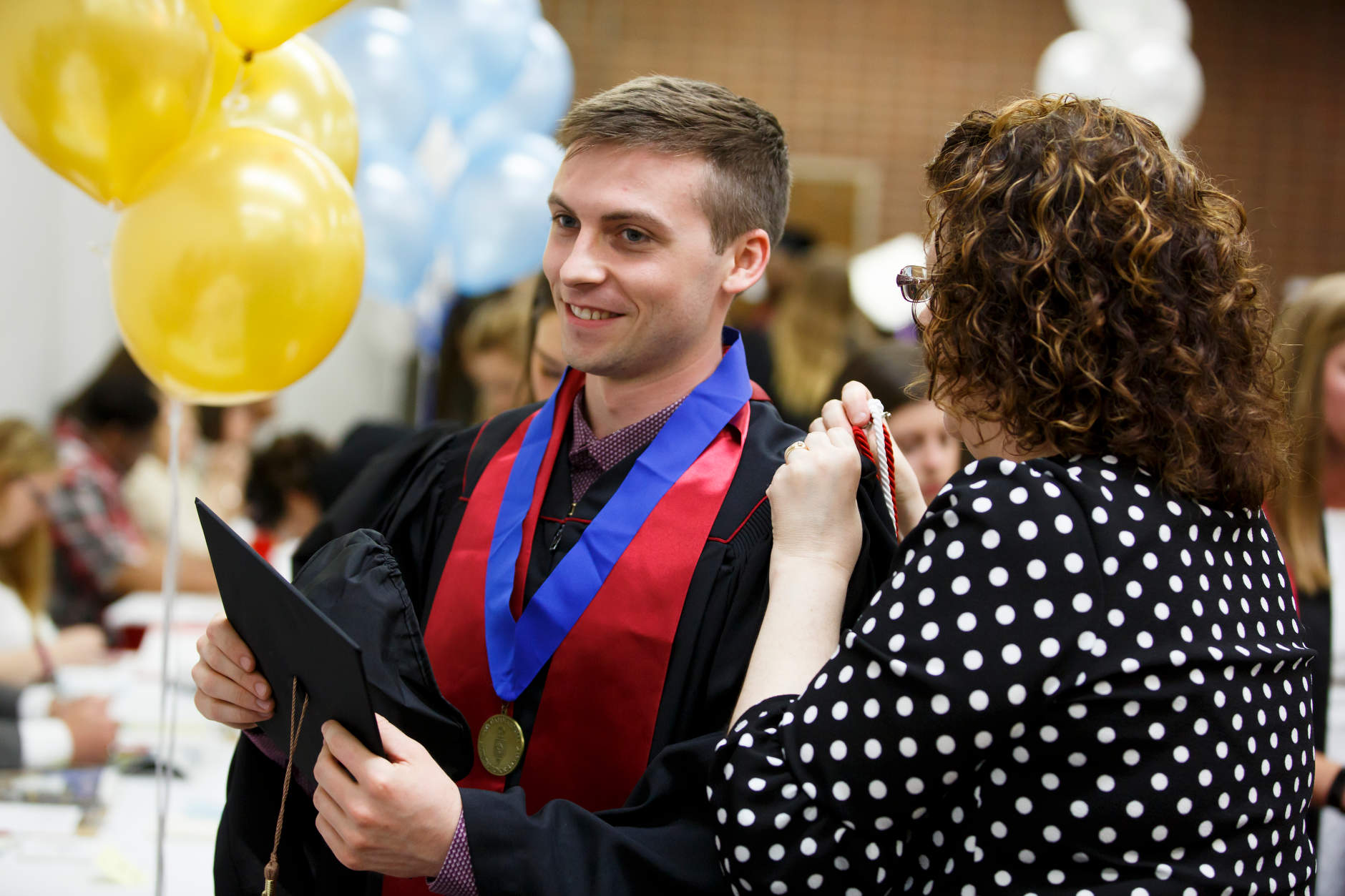 A volunteer assists a graduate with chords before the IU Northwest Commencement at the Genesis Convention Center on Thursday, May 9, 2019. (James Brosher/Indiana University)