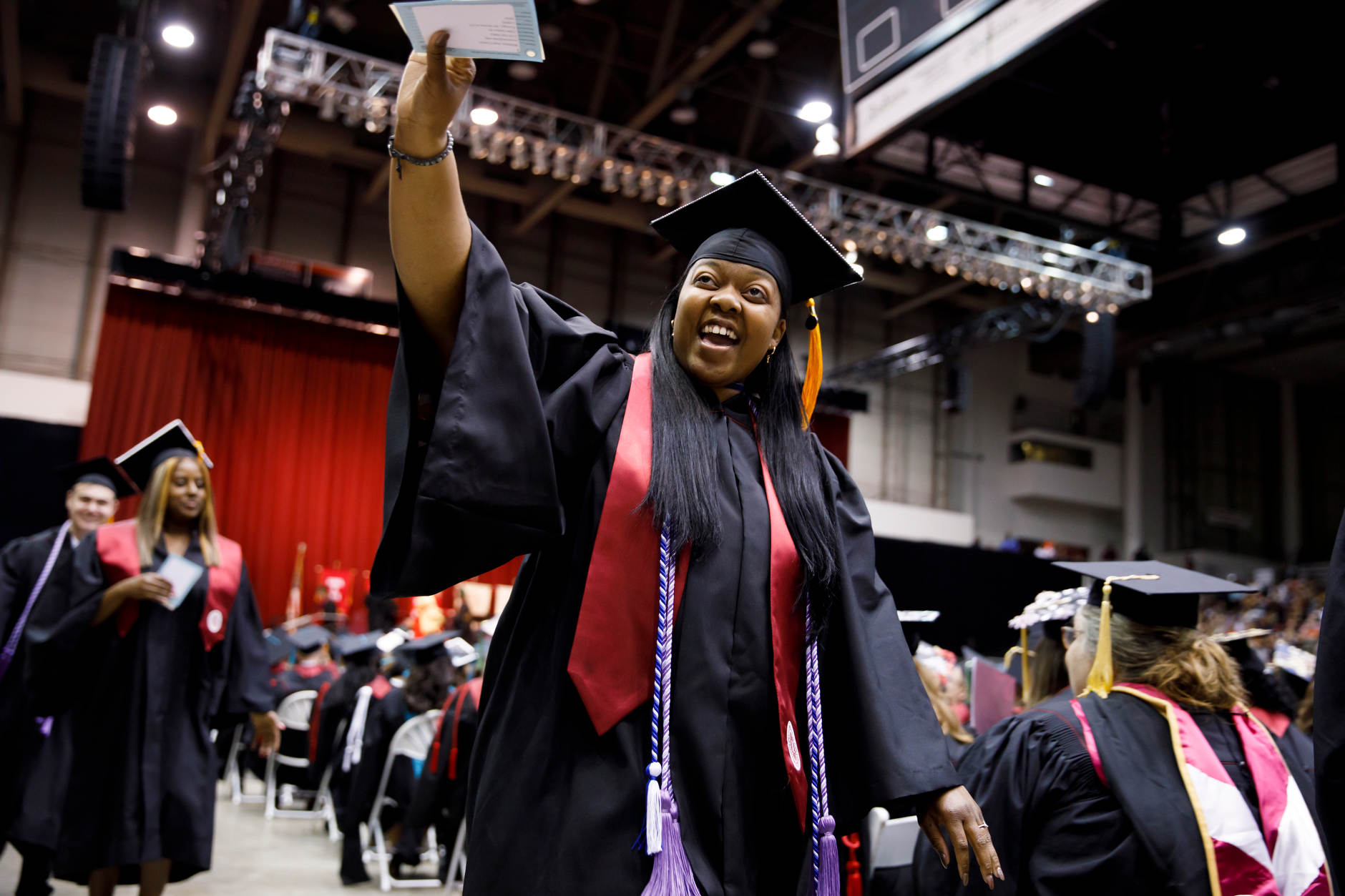 A graduate waves to friends in the audience during the IU Northwest Commencement at the Genesis Convention Center on Thursday, May 9, 2019. (James Brosher/Indiana University)