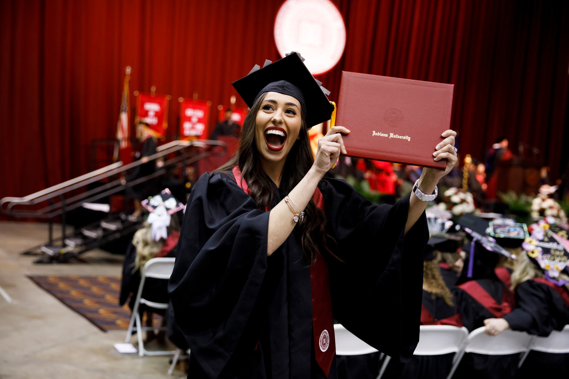 A graduate celebrates after receiving her diploma during the Indiana University Northwest Commencement at the Genesis Convention Center on Thursday, May 9, 2019. (James Brosher/Indiana University)