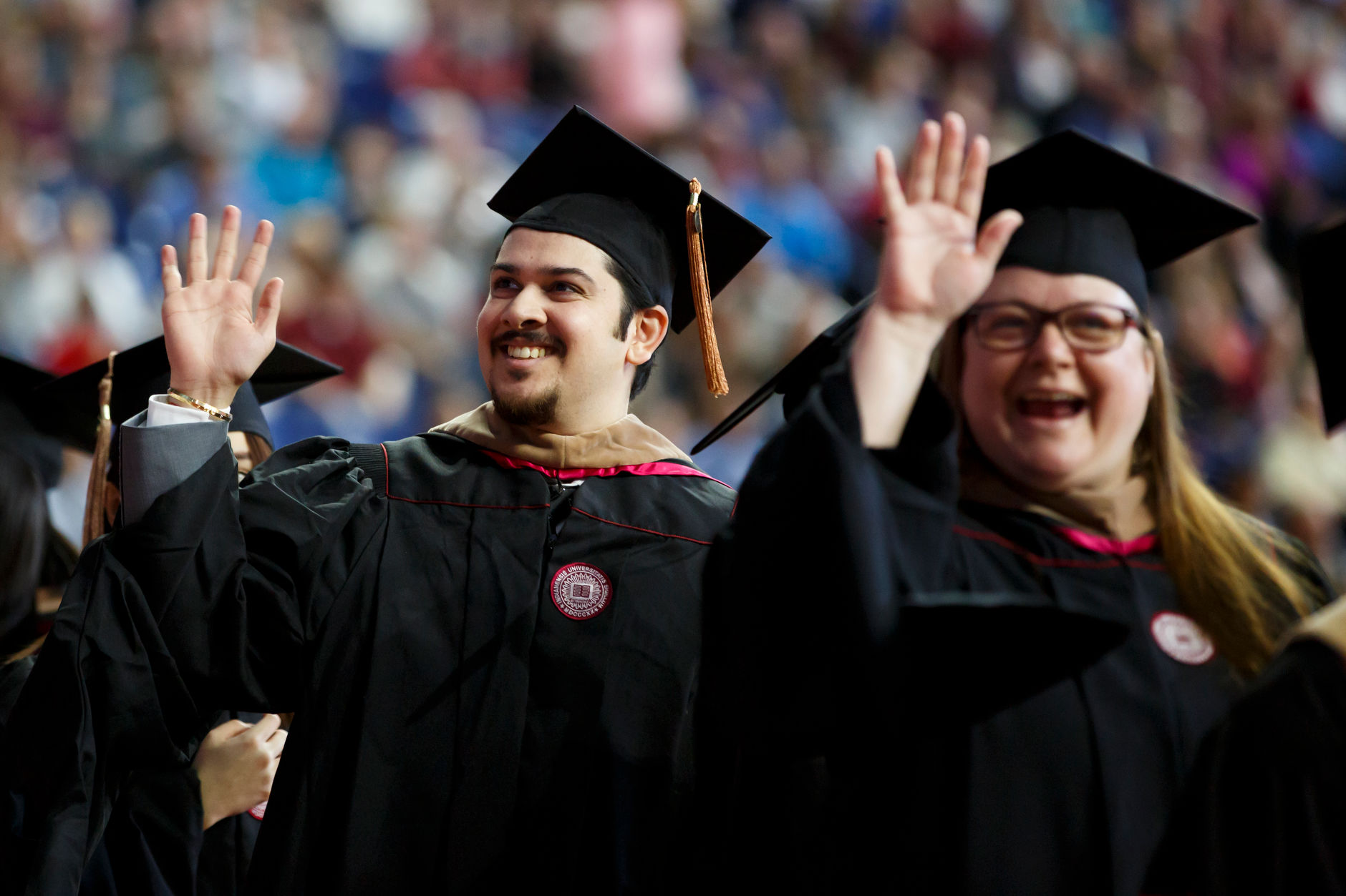 Graduates wave to friends in the audience during the IUPUI Commencement at Lucas Oil Stadium on Saturday, May 11, 2019. (James Brosher/Indiana University)