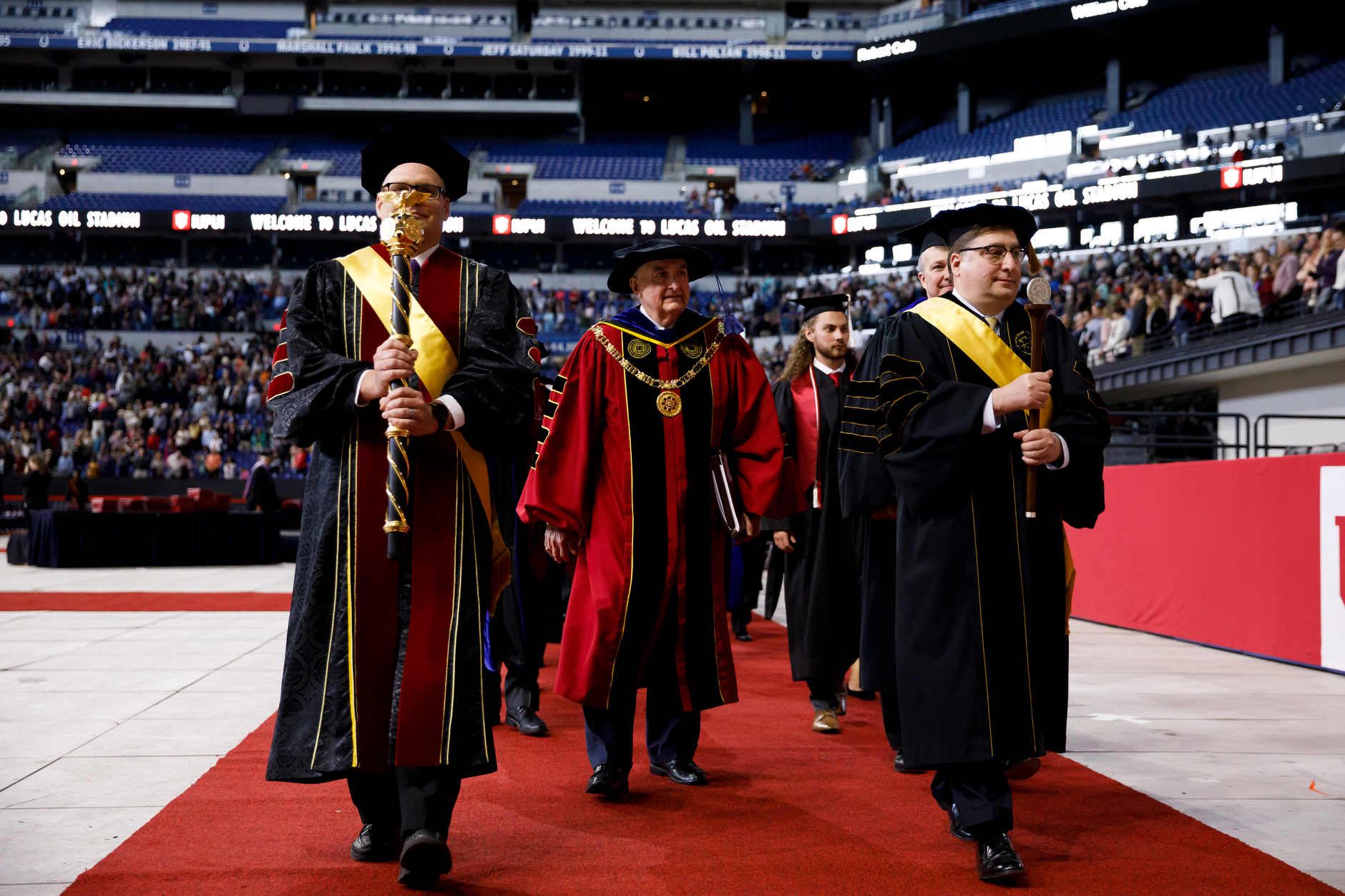 Indiana University President Michael A. McRobbie, center, walks in the recessional during the IUPUI Commencement at Lucas Oil Stadium on Saturday, May 11, 2019. (James Brosher/Indiana University)