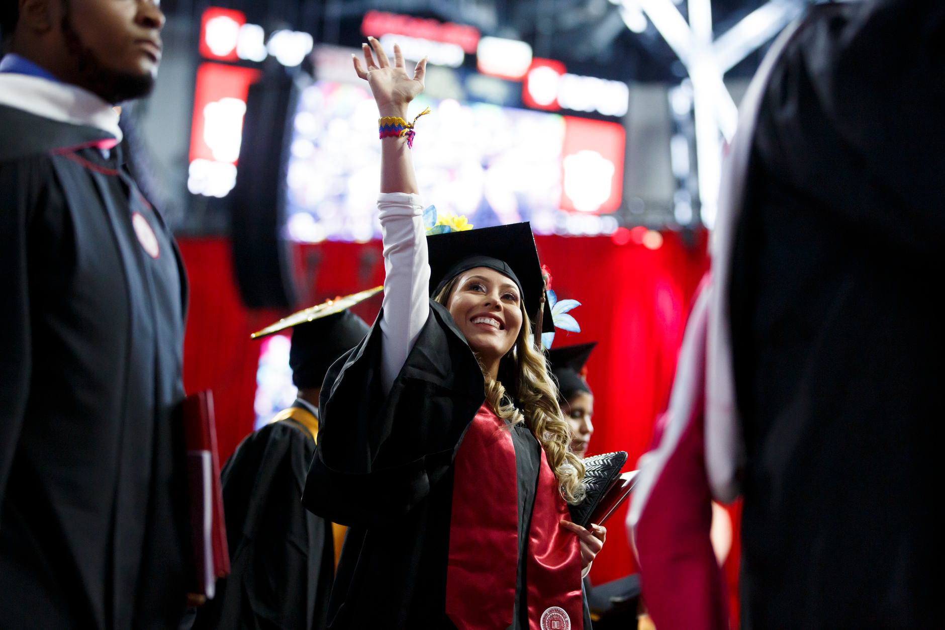 A graduate waves to friends in the audience during the recessional at IUPUI Commencement at Lucas Oil Stadium on Saturday, May 11, 2019. (James Brosher/Indiana University)
