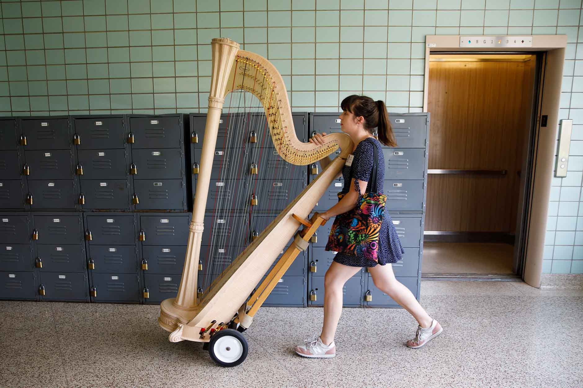 USA International Harp Competition Coordinator Caroline Robinson moves a harp during the 11th USA International Harp Competition at Indiana University in Bloomington, Indiana on Wednesday, July 3, 2019. (Photo by James Brosher)