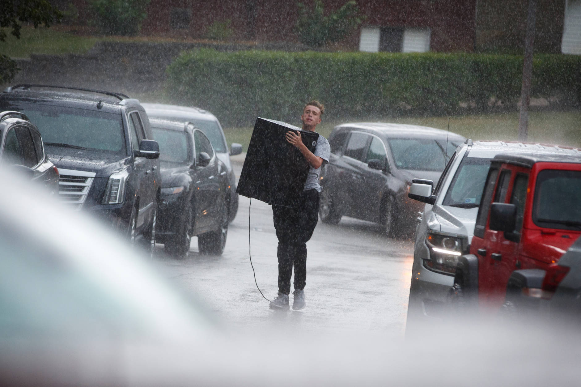 A student carries a mini fridge through a downpour during IU Bloomington move-in at Forest Quad on Tuesday, Aug. 20, 2019. (James Brosher/Indiana University)