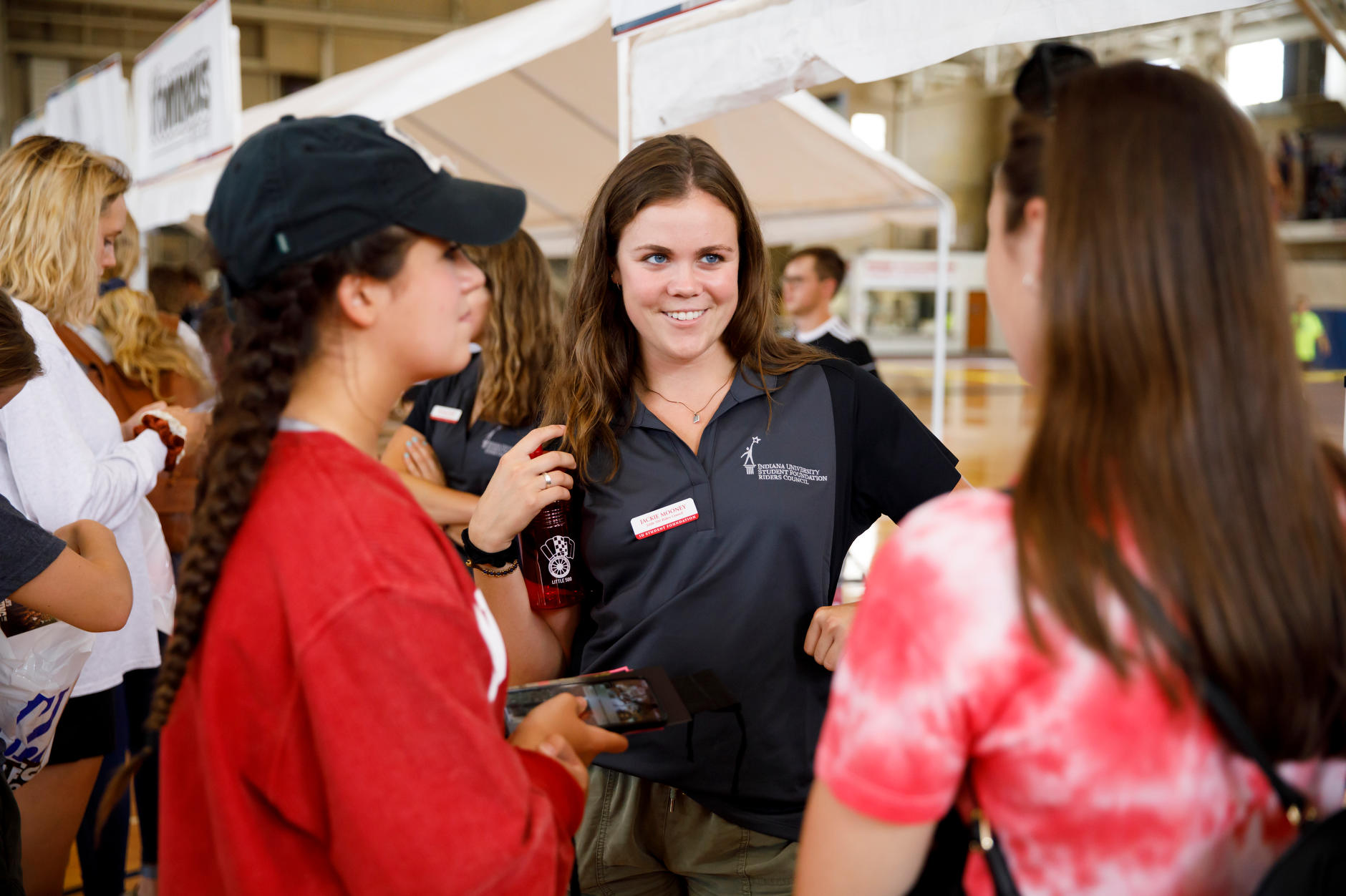 Little 500 Riders Council member Jackie Mooney speaks to a student at the Indiana University Student Foundation booth during RecFest in the Intramural Center at IU Bloomington on Friday, Aug. 23, 2019. (James Brosher/Indiana University)