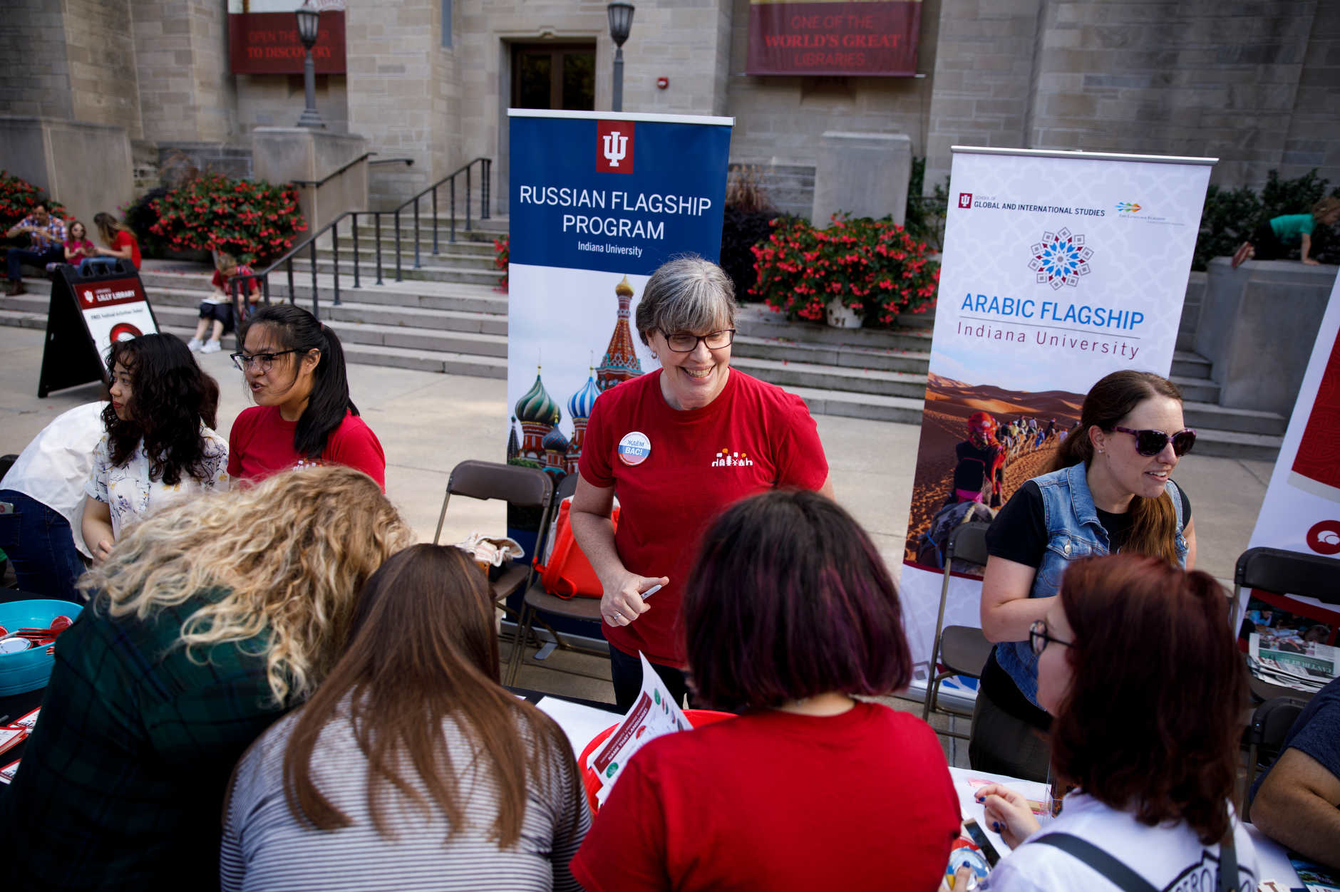 Indiana University Hamilton Lugar School of Global and International Studies Summer Language Workshop Director Kathleen Evans, center, greets visitors at the programÕs table during the First Thursdays Festival on the Arts Plaza at IU Bloomington on Thursday, Sept. 5, 2019. (James Brosher/Indiana University)