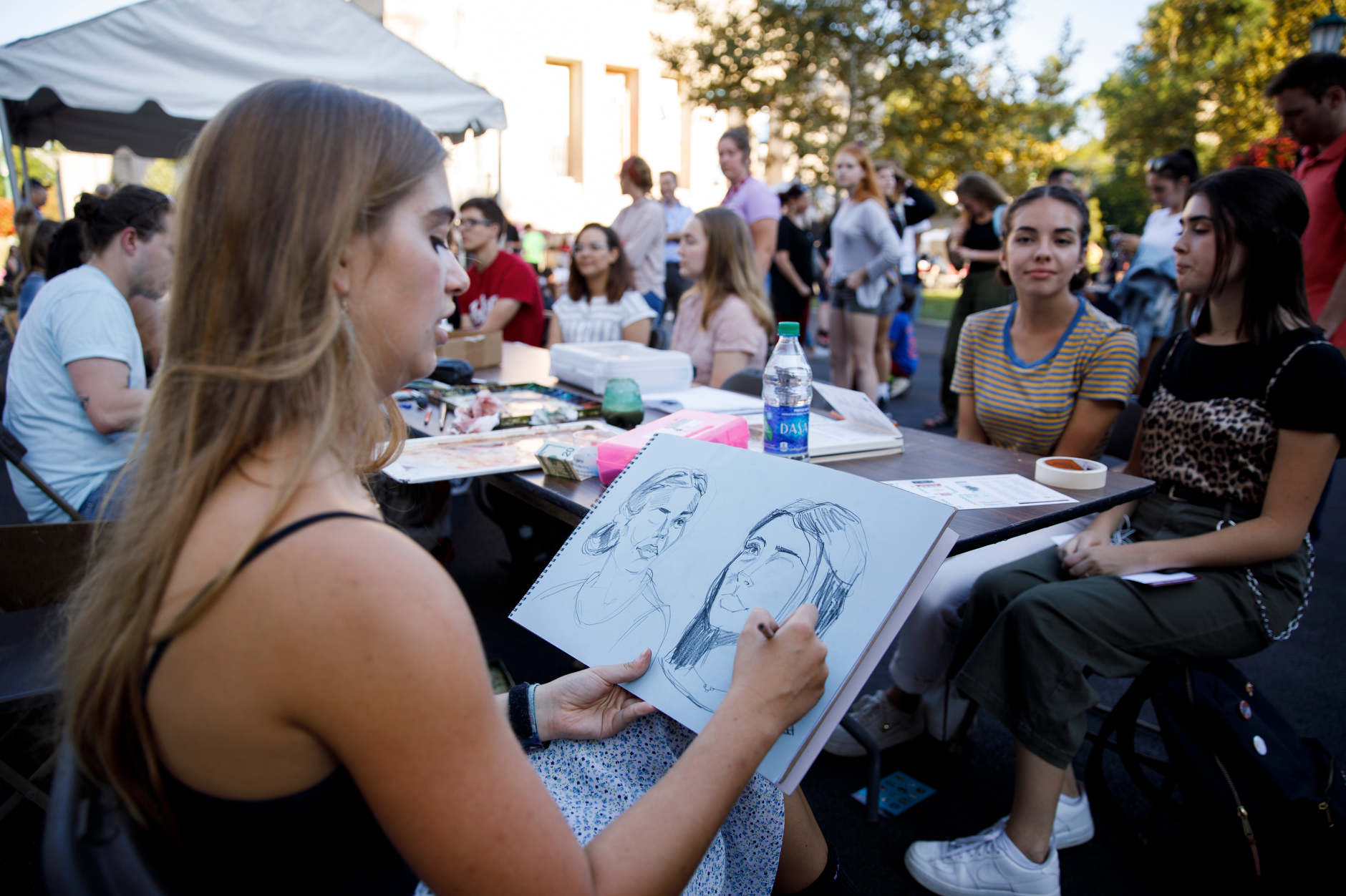 A portrait artist draws two students outside the Indiana University Eskenazi School of Art, Architecture + Design during the First Thursdays Festival on the Arts Plaza at IU Bloomington on Thursday, Sept. 5, 2019. (James Brosher/Indiana University)