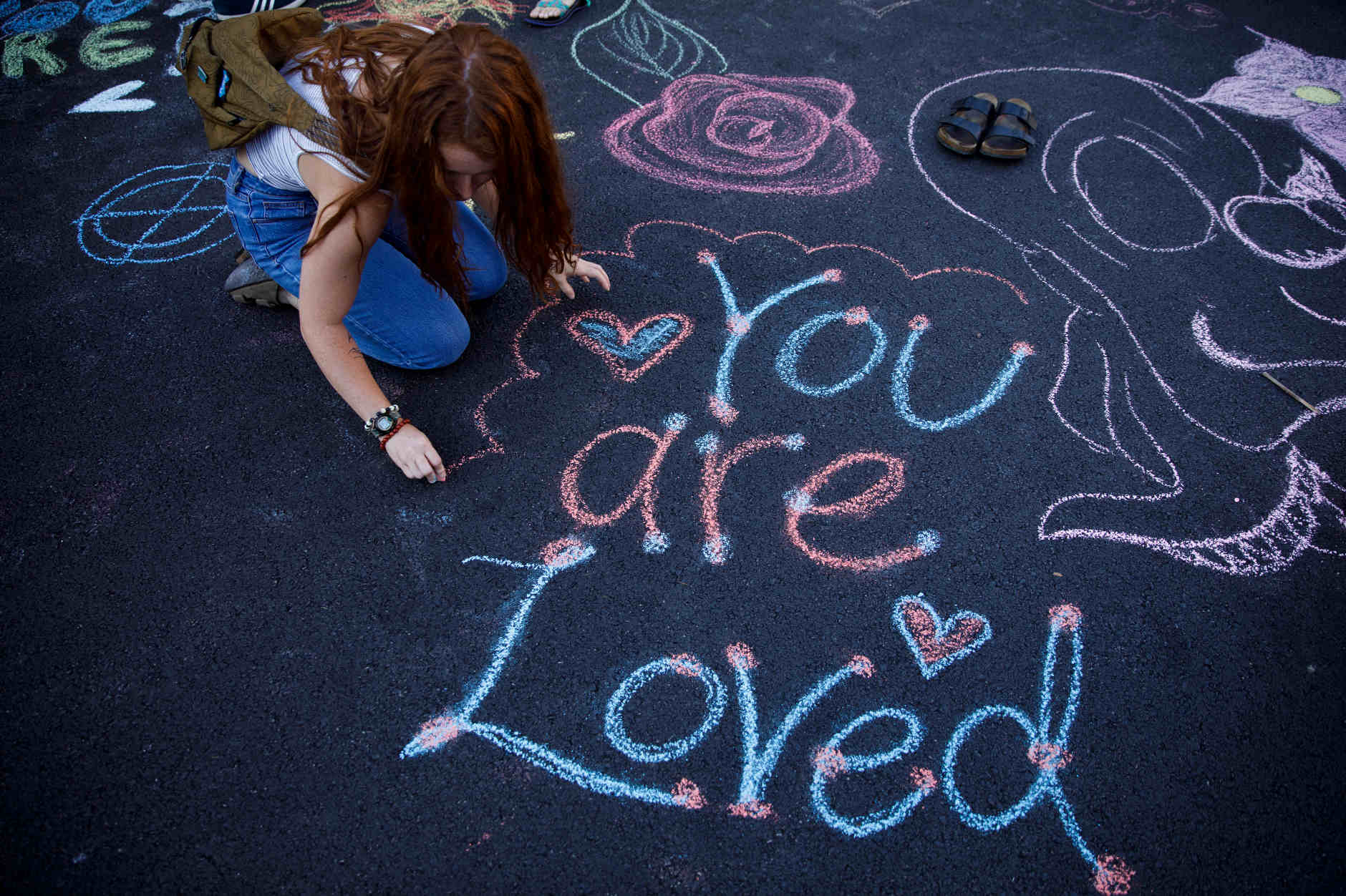 A student writes a message on the pavement using sidewalk chalk during the First Thursdays Festival on the Arts Plaza at IU Bloomington on Thursday, Sept. 5, 2019. (James Brosher/Indiana University)