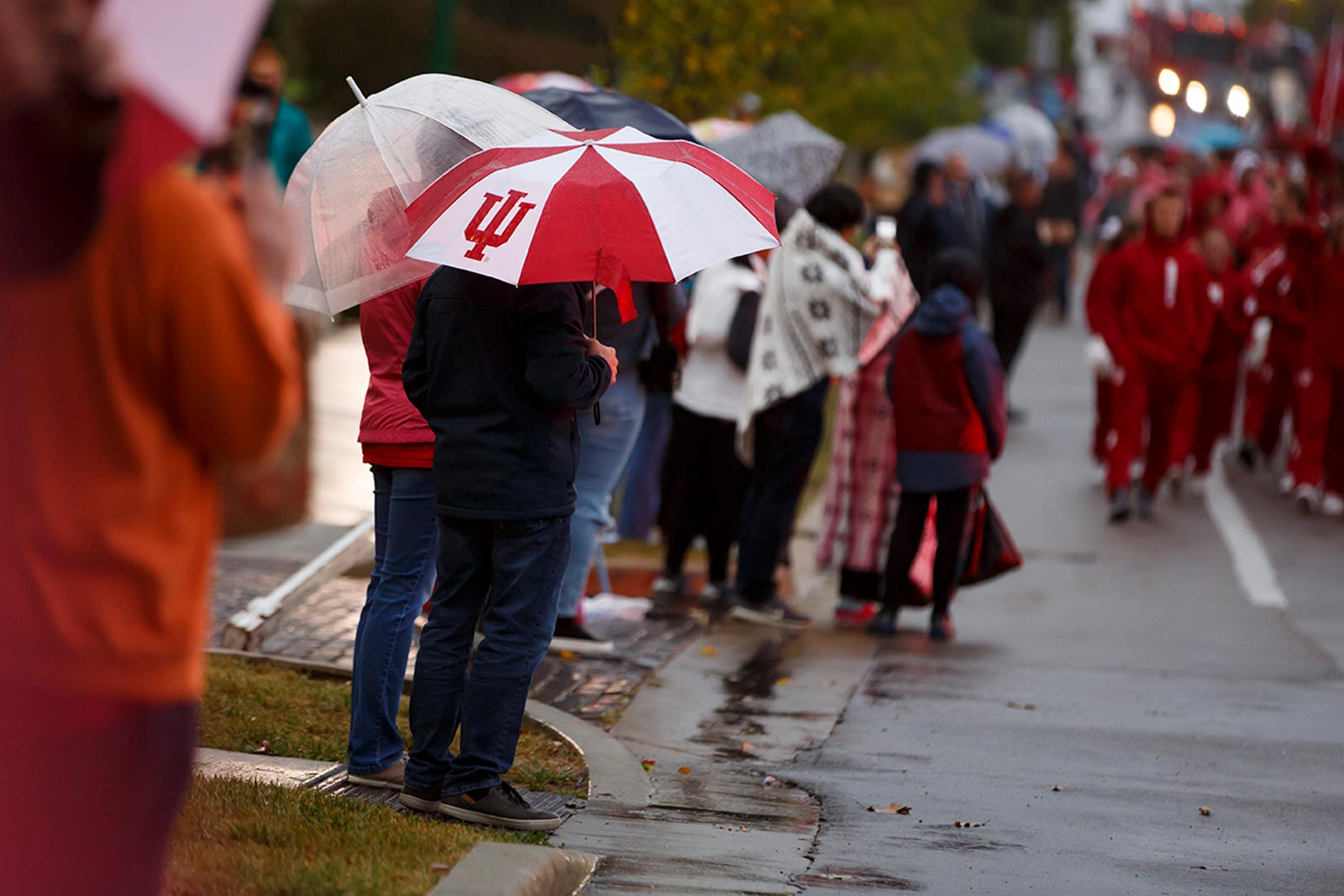An IU umbrella shields a parade goer from the rain along Woodlawn Avenue during the IU Bloomington Homecoming Parade on Friday, Oct. 11, 2019. (James Brosher/Indiana University)