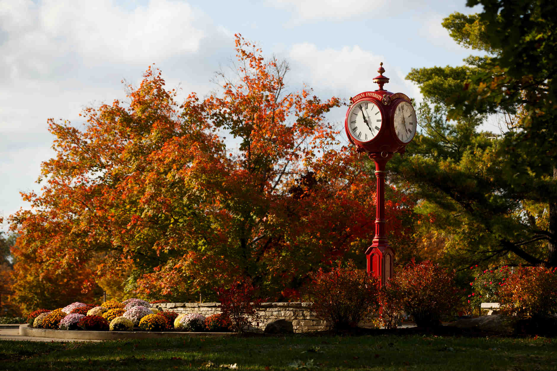 Fall foliage is pictured behind one of Indiana University's iconic red clocks near Woodburn Hall at IU Bloomington on Tuesday, Oct. 22, 2019. (James Brosher/Indiana University)