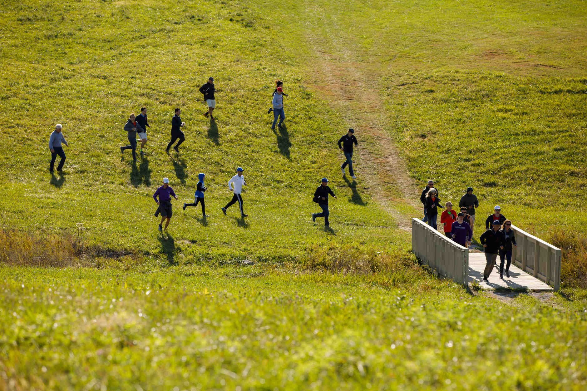 Spectators race across a field to get a glimpse of runners on the backstretch during the Indiana State Pre-National Cross Country Invitational in Terre Haute, Indiana on Saturday, Oct. 19, 2019. (Photo by James Brosher)