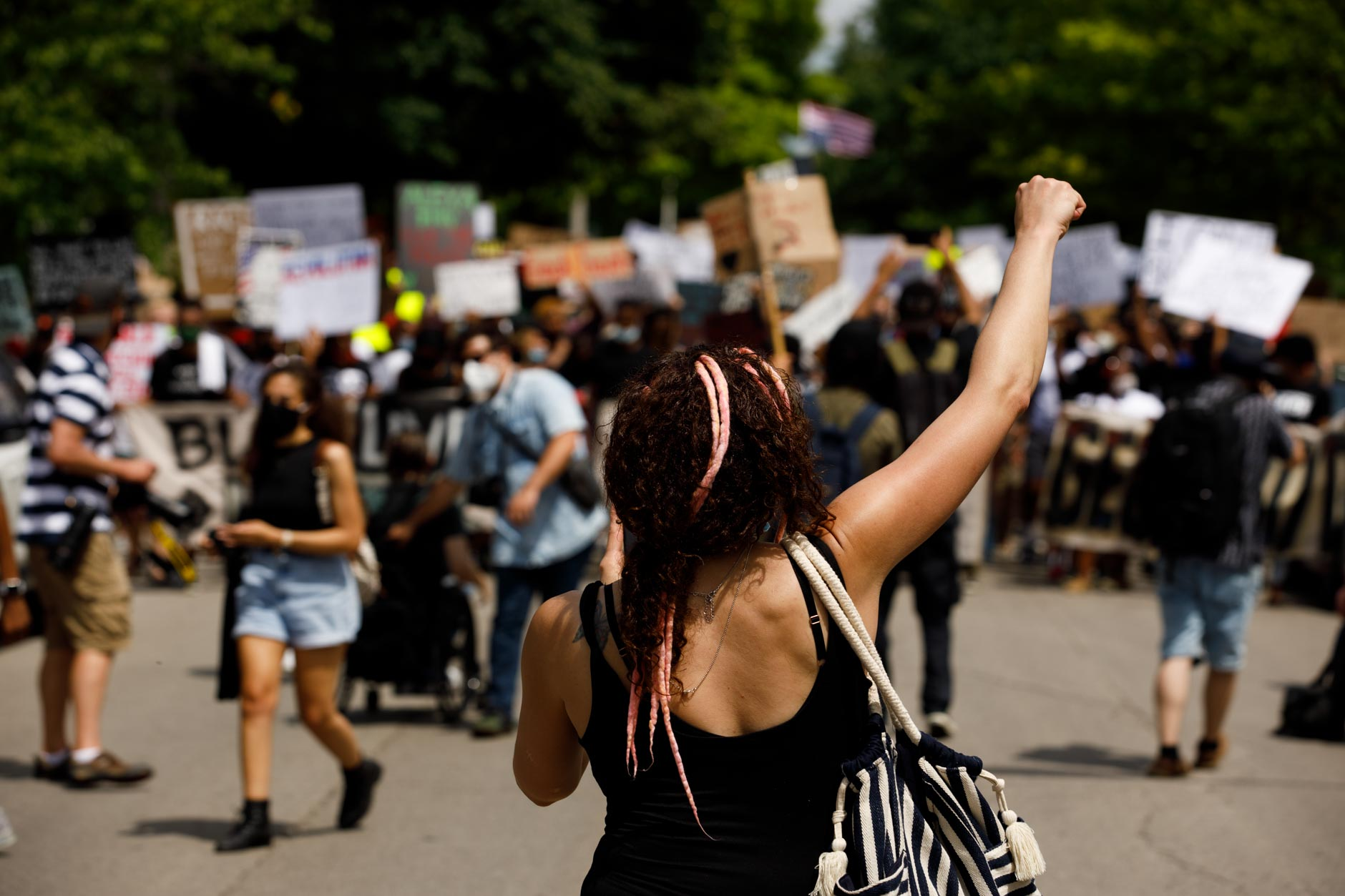 A woman raises her fist in solidarity with Black Lives Matter protestors as a group of hundreds march from Dunn Meadow at Indiana University Bloomington to the Monroe County Courthouse square on Friday, June 5, 2020. (James Brosher/Indiana University)