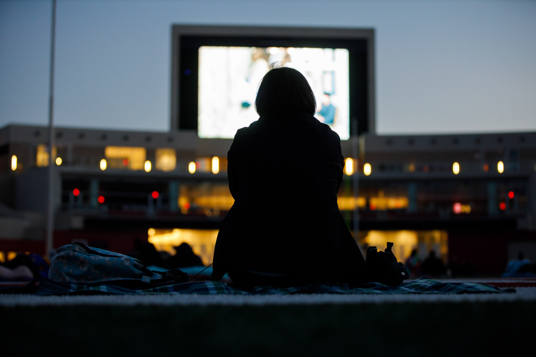 "An audience member watches a socially-distant screening of ""Cinema Paradiso"" from the field in Memorial Stadium at IU Bloomington on Tuesday, Sept. 29, 2020. (James Brosher/Indiana University)"