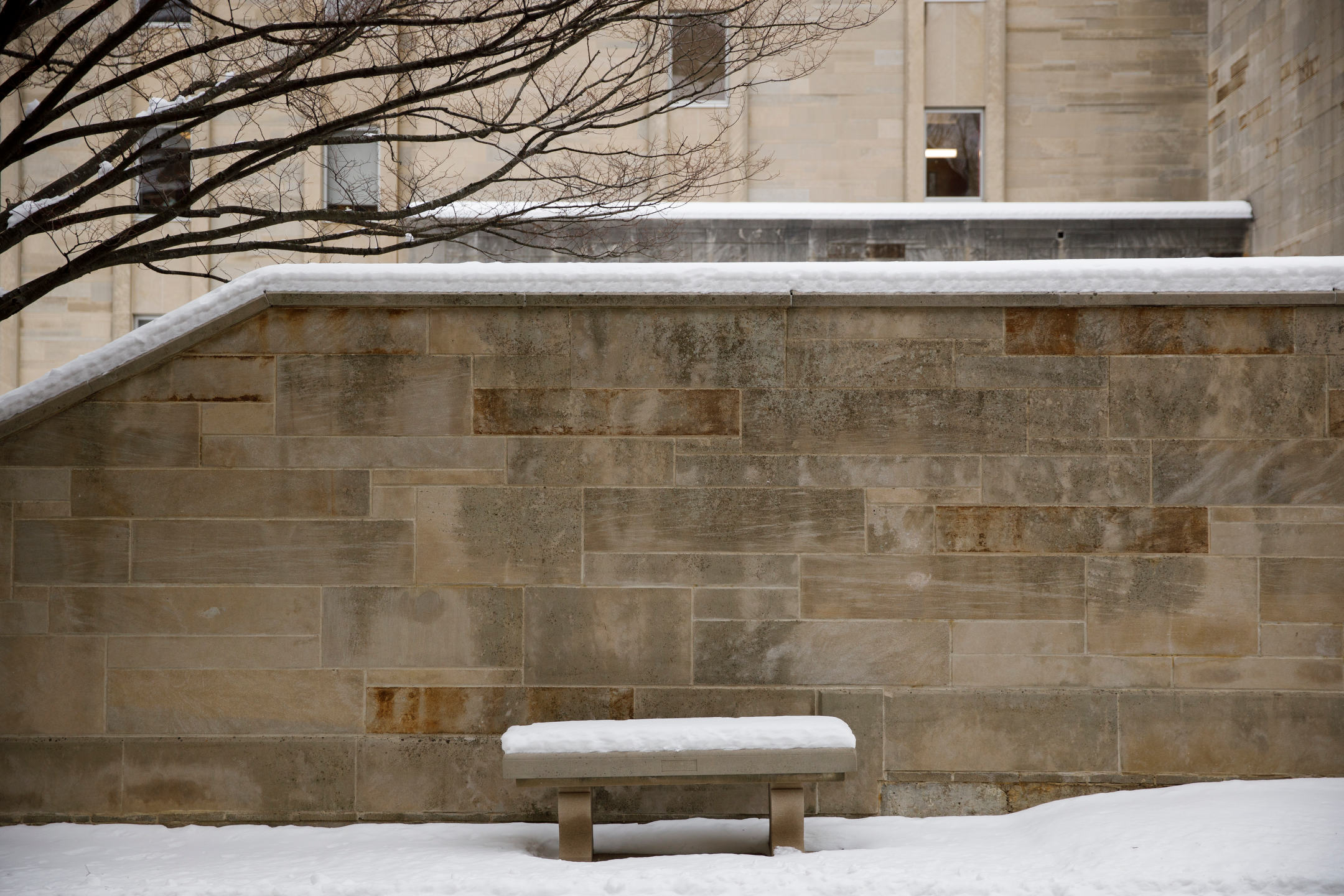Snow covers a bench and wall near the Chemistry Building on a winter day at Indiana University Bloomington on Wednesday, Feb. 10, 2021.