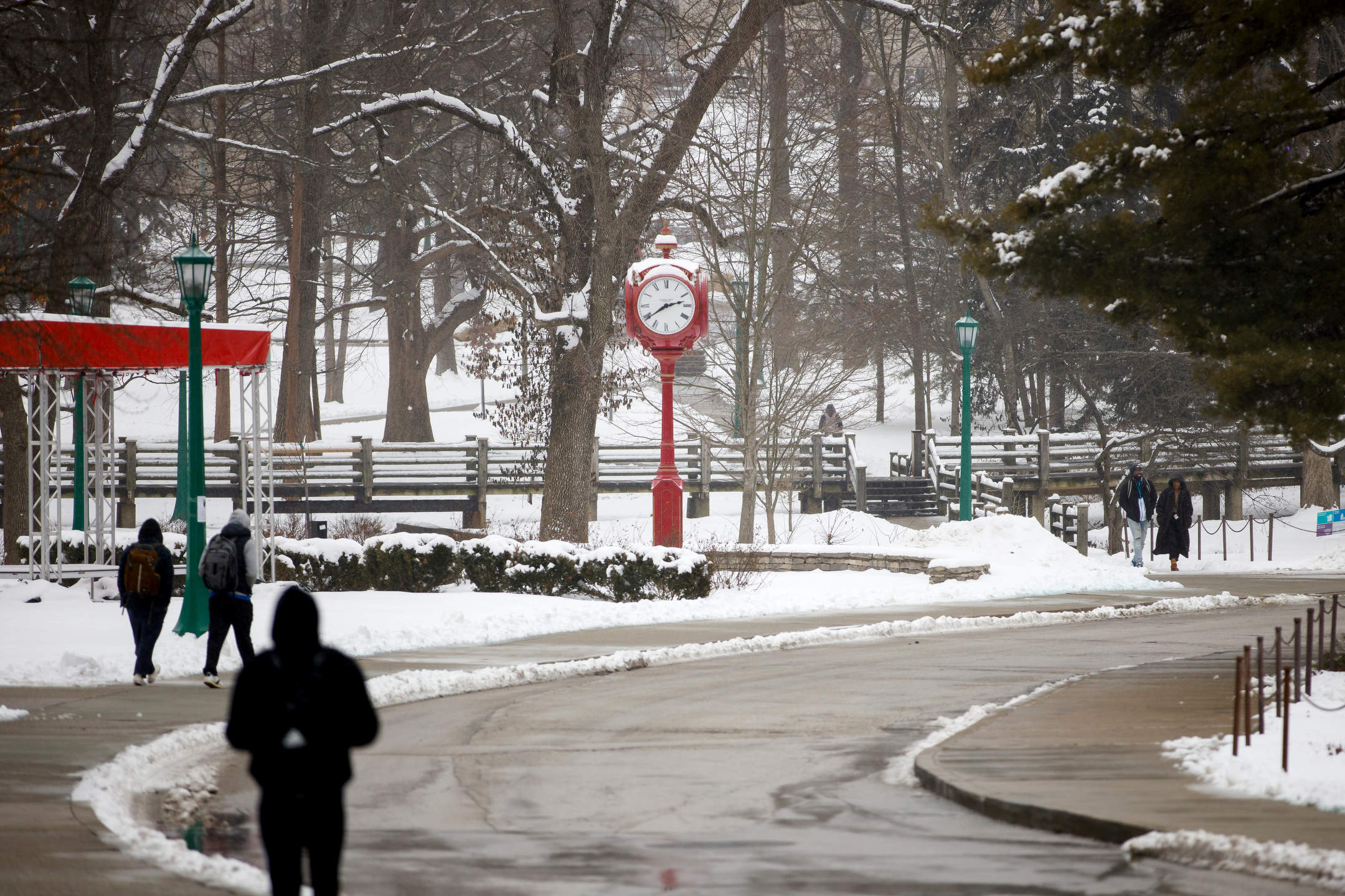 Students walk to classes past a red clock near Woodburn Hall on a winter day at Indiana University Bloomington on Wednesday, Feb. 10, 2021.