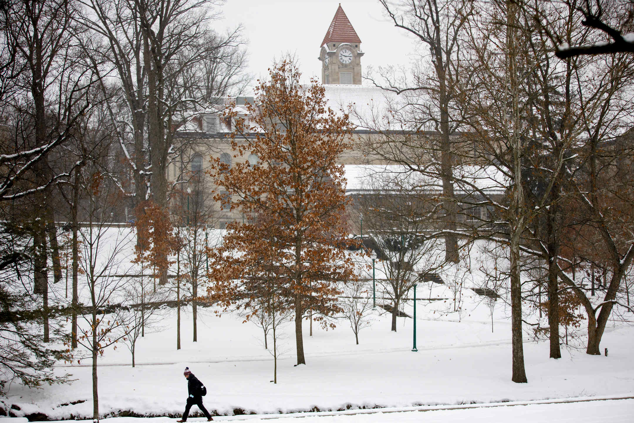 A student walks through a snow-covered Dunn Meadow on a winter day at Indiana University Bloomington on Wednesday, Feb. 10, 2021. Pictured in background is the Student Building clock tower.